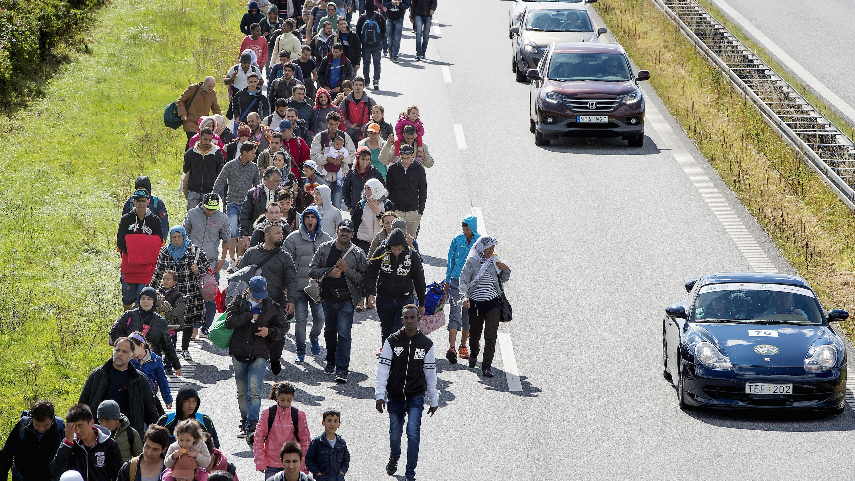 Migrants stream northward on a Danish highway.