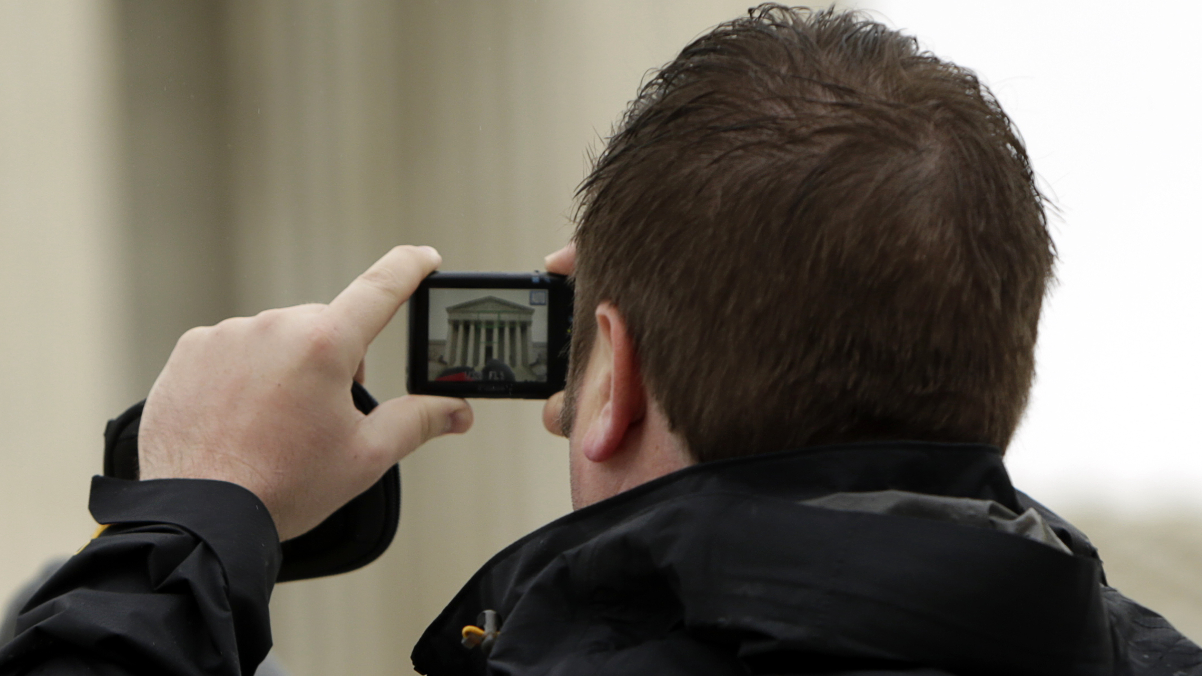 A man takes a picture with his mobile device outside of the U.S. Supreme Court in Washington April 29, 2014. The U.S. Supreme Court on Tuesday confronts the question of whether the increasing amount of deeply personal information kept on mobile devices means police officers need a warrant before they can search an arrested suspect's cell phone.