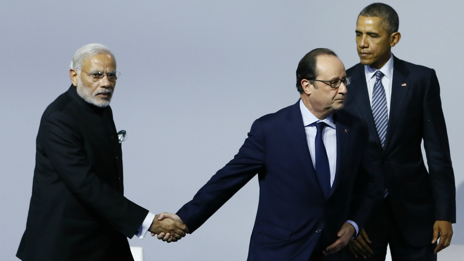 French President Francois Hollande, center, shakes hands with Indian Prime Minister Narendra Modi, left, as US President Barack Obama leaves the 'Mission Innovation: Accelerating the Clean Energy Revolution' meeting at the COP2, United Nations Climate Change Conference, in Le Bourget, north of Paris, Monday, Nov. 30 2015. (Ian Langsdon, Pool photo via AP)