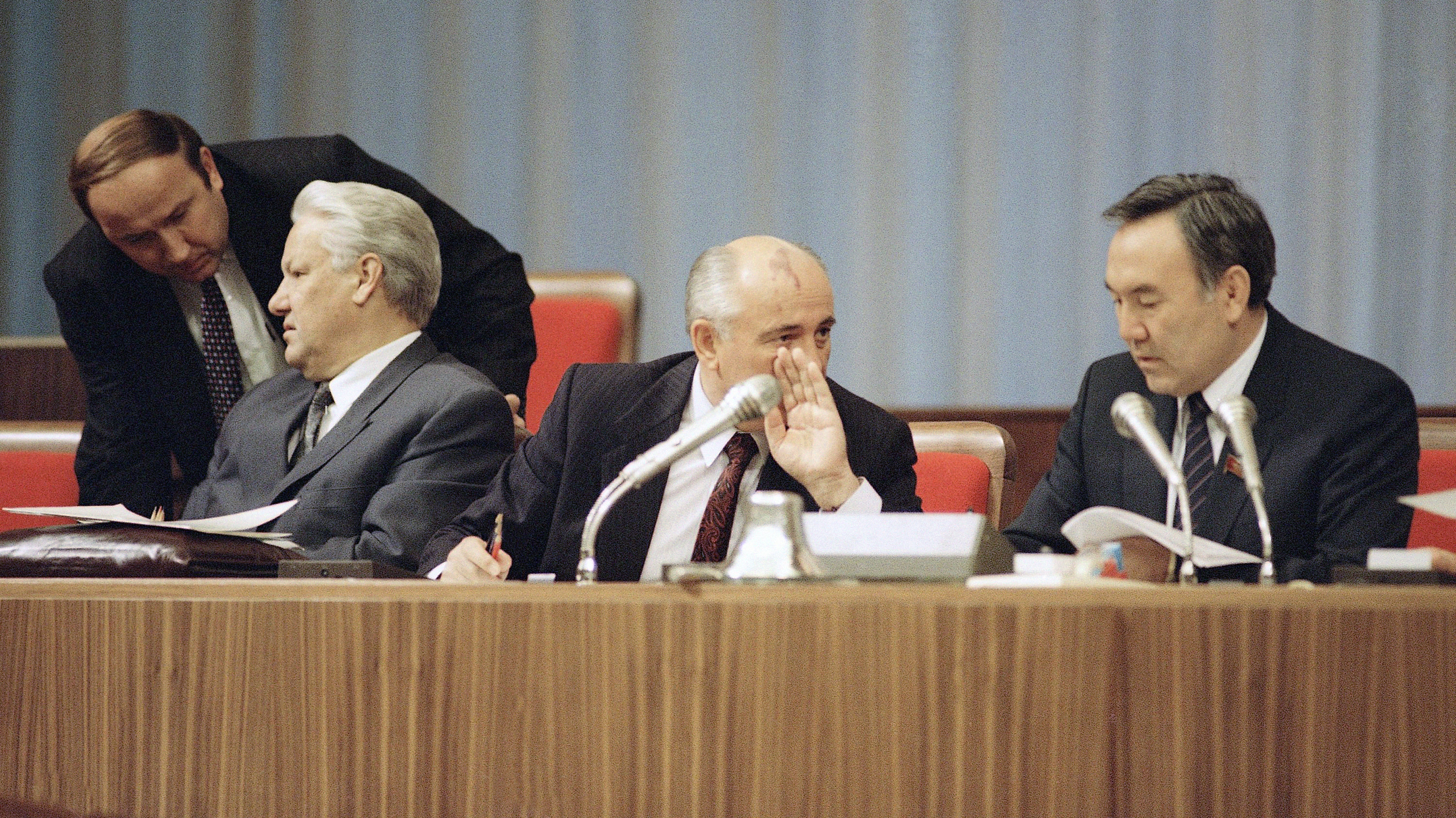 Soviet President Mikhail Gorbachev, center, whispes behind his hand to Nursultan Nazarbayev, President of Kazakhstan, as Russian President Boris Yeltsin, seated left, confers with a security guard during special session of the Congress of People's Deputies at the Kremlin, Moscow on Tuesday, Sept. 3, 1991.