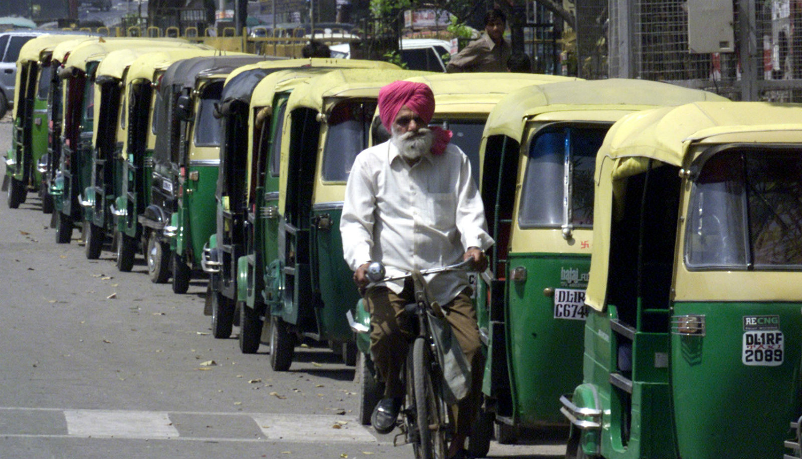 A cyclist passes by a queue of auto-rickshaws waiting to fill their tanks at station selling compressed natural gas in New Delhi April 2, 2001. Commuters in the Indian capital were stranded for a second day running on Monday as thousands of buses and taxis went off the roads under a court order to switch to the cleaner fuel. Some 15,000 private and state-run buses and thousands of taxis and three-wheelers had been ordered by the Supreme Court to change to compressed natural gas from diesel by April 1 in a drive to clean the capital's dirty air.