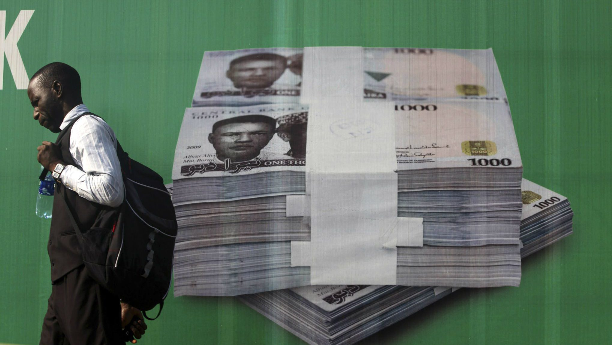 A man walks past a promotional banner showing a photograph of a pile of Nigerian naira along a road in Lagos November 24, 2010. The Nigerian naira eased further on the interbank market and at the official window on Wednesday as strong demand for dollars put pressure on the local currency, traders said. REUTERS/Akintunde Akinleye (NIGERIA - Tags: BUSINESS)