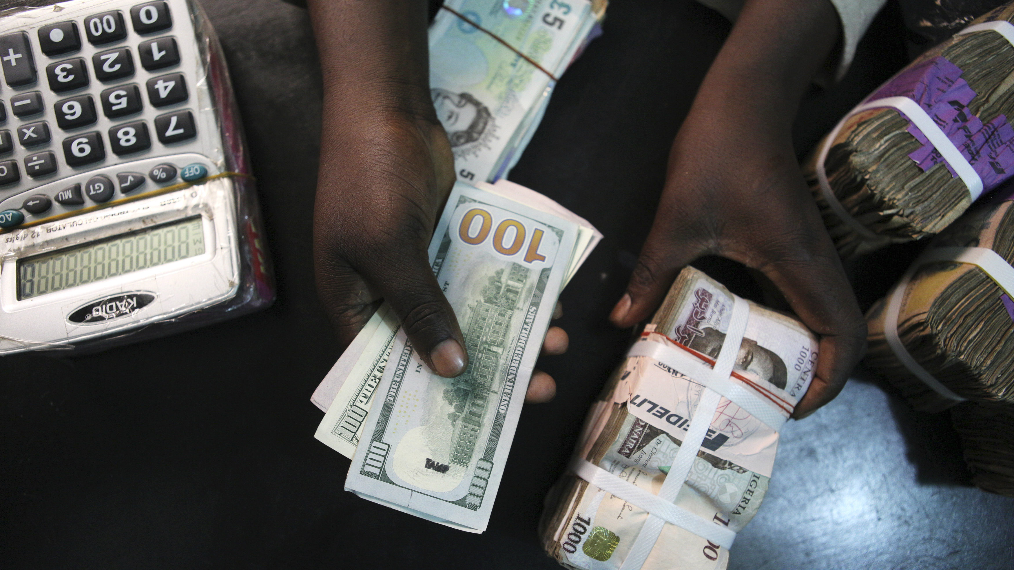 A trader changes dollars for Naira at a currency exchange store in Lagos, February 12, 2015. REUTERS/Joe Penney (NIGERIA - Tags: ELECTIONS POLITICS BUSINESS)