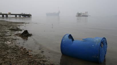 An idle oil exploration vessel (L) is shrouded by haze in the Johor River in Malaysia's southern state of Johor..