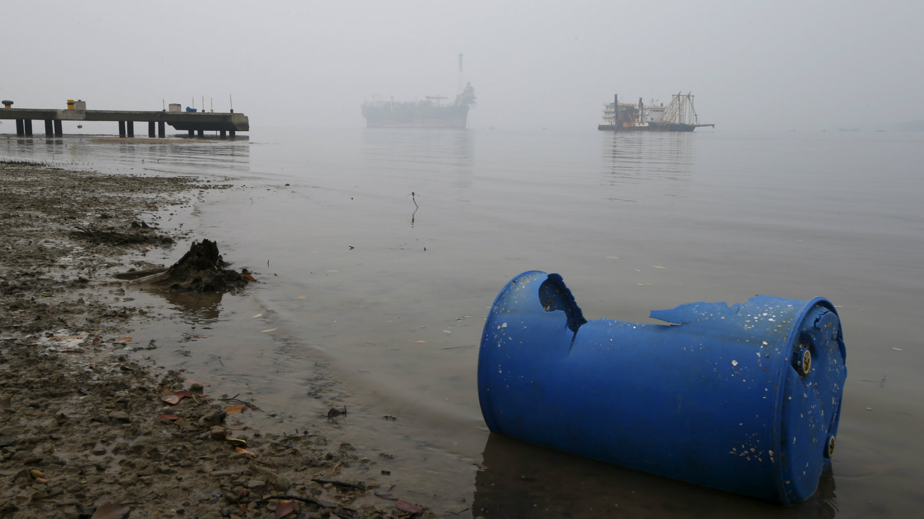 An idle oil exploration vessel (L) is shrouded by haze in the Johor River in Malaysia's southern state of Johor October 6, 2015. Renewables are powering a rare bright spot in the energy industry, with record job hiring in solar, wind and hydro partly offsetting the biggest round of job losses in the oil and gas sector in almost two decades. The boom in new green jobs is being led by Asia where governments in countries such as China and India are embarking on massive programmes to use more renewable energy. Picture taken October 6, 2015. To match ENERGY-EMPLOYMENT/ REUTERS/Edgar Su