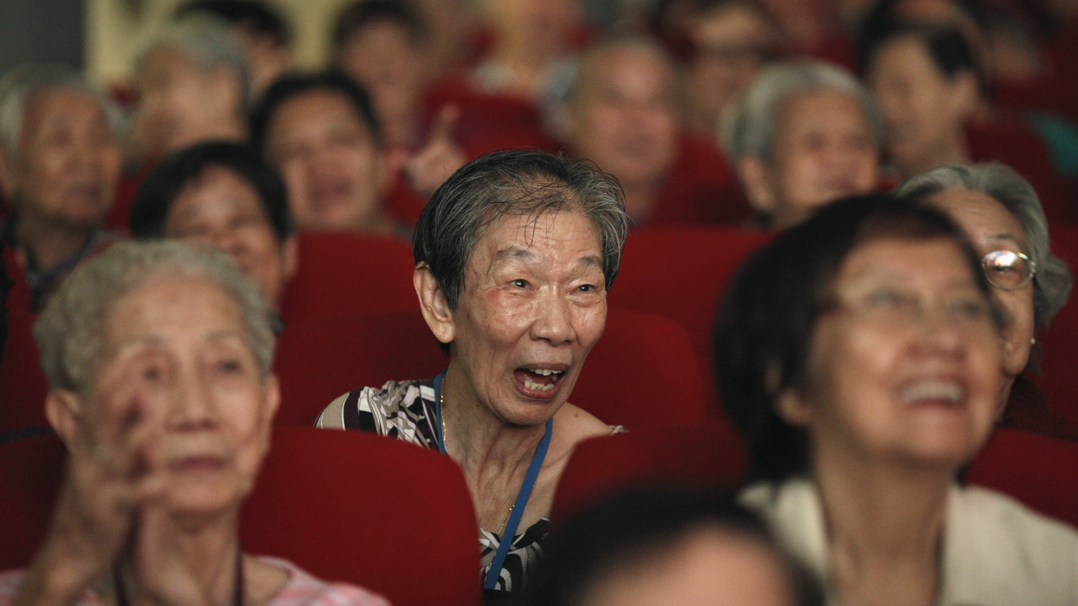 An elderly woman laughs as she watches a free Chinese opera performance ahead of Lunar New Year in Singapore January 10, 2014. The opera show was organised by Shan You, a voluntary welfare organisation, which was raising funds to continue their services to the elderly. REUTERS/Edgar Su (SINGAPORE - Tags: SOCIETY)
