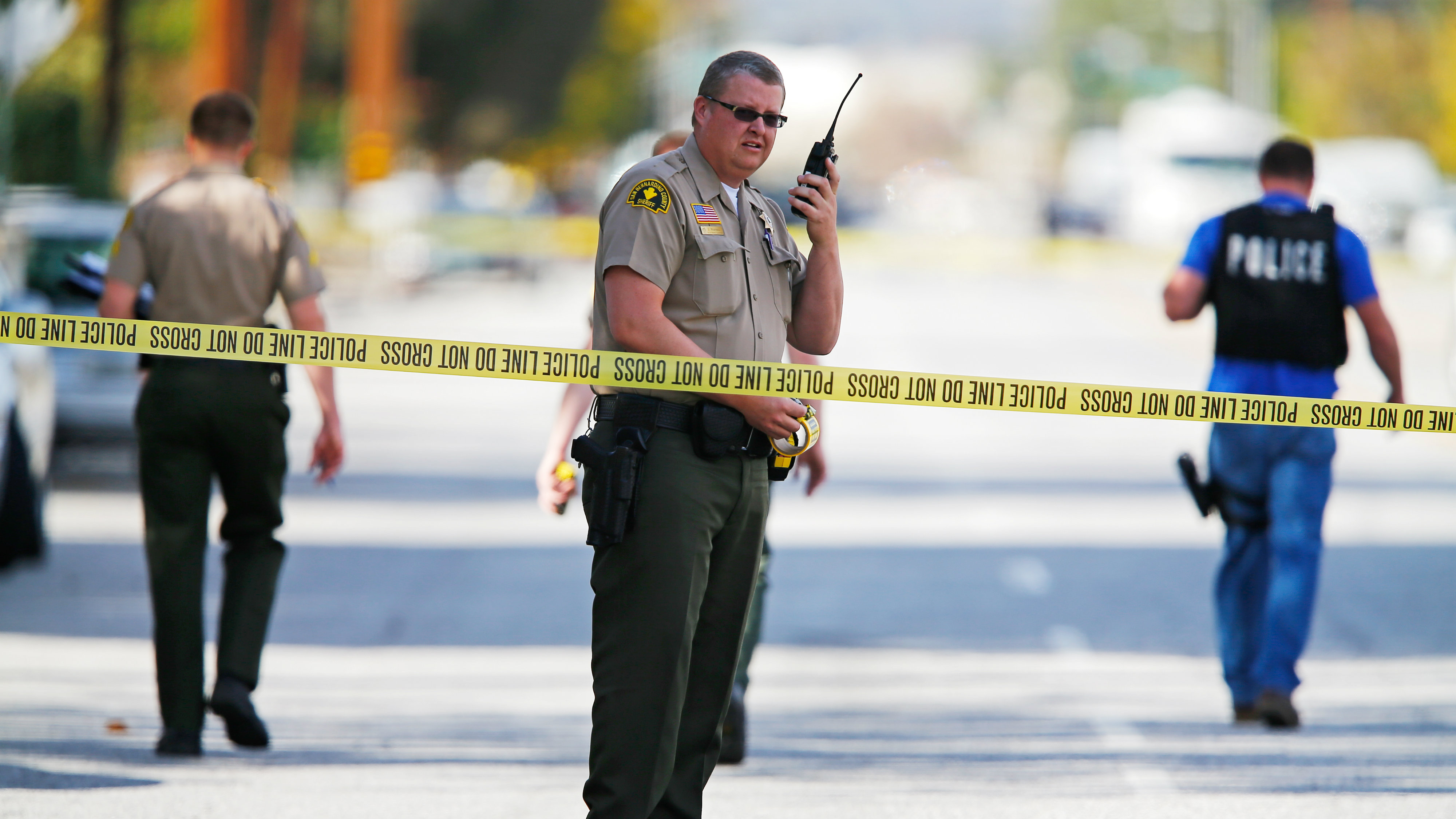FBI and police investigators examine evidence at the scene of the investigation around the area of the SUV vehicle where two suspects were shot by police following a mass shooting in San Bernardino, California December 3, 2015. Authorities on Thursday were working to determine why Syed Rizwan Farook 28, and Tashfeen Malik, 27, opened fire at a holiday party of his co-workers in Southern California, killing 14 people and wounding 17 in an attack that appeared to have been planned.