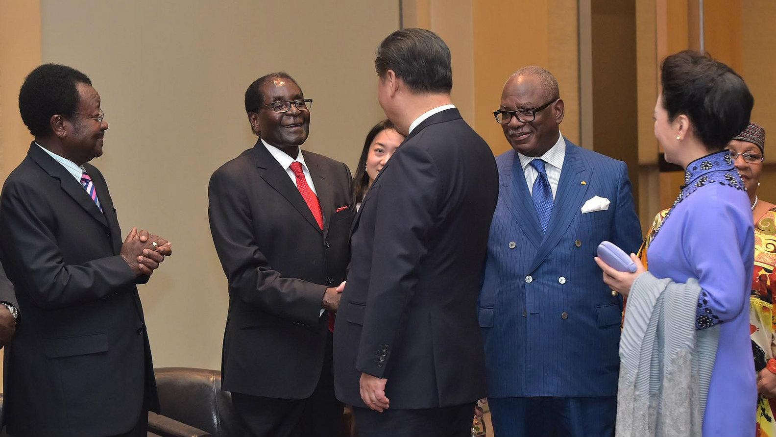 Zimbabwe's Robert Mugabe shakes hands with Chinese president Xi Jinping.