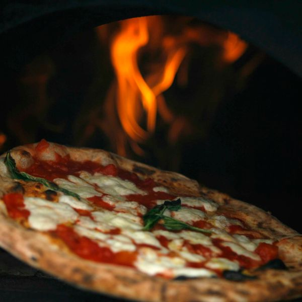 "A pizza is removed from a wood-burning oven during a protest to demand stricter price controls on the rising cost of pizza in Naples August 27, 2008. ""Pizzaioli"" or pizza chefs in Naples, birthplace of the Margherita, handed out free pizzas on Wednesday in protest at high prices charged by rivals who, they say, use the spike in commodity prices to rip off consumers. In the city where the classic ""Margherita"" with mozzarella, tomato and basil topping was invented in the 19th century - and named in honour of a queen with a taste for fast food - 30 cooks lit up six wood-burning ovens to cook 5,000 thin-crusted Neapolitan pizzas for queues of local people and tourists.  REUTERS/Ciro De Luca/Agnfoto (ITALY) - RTR21QSC"