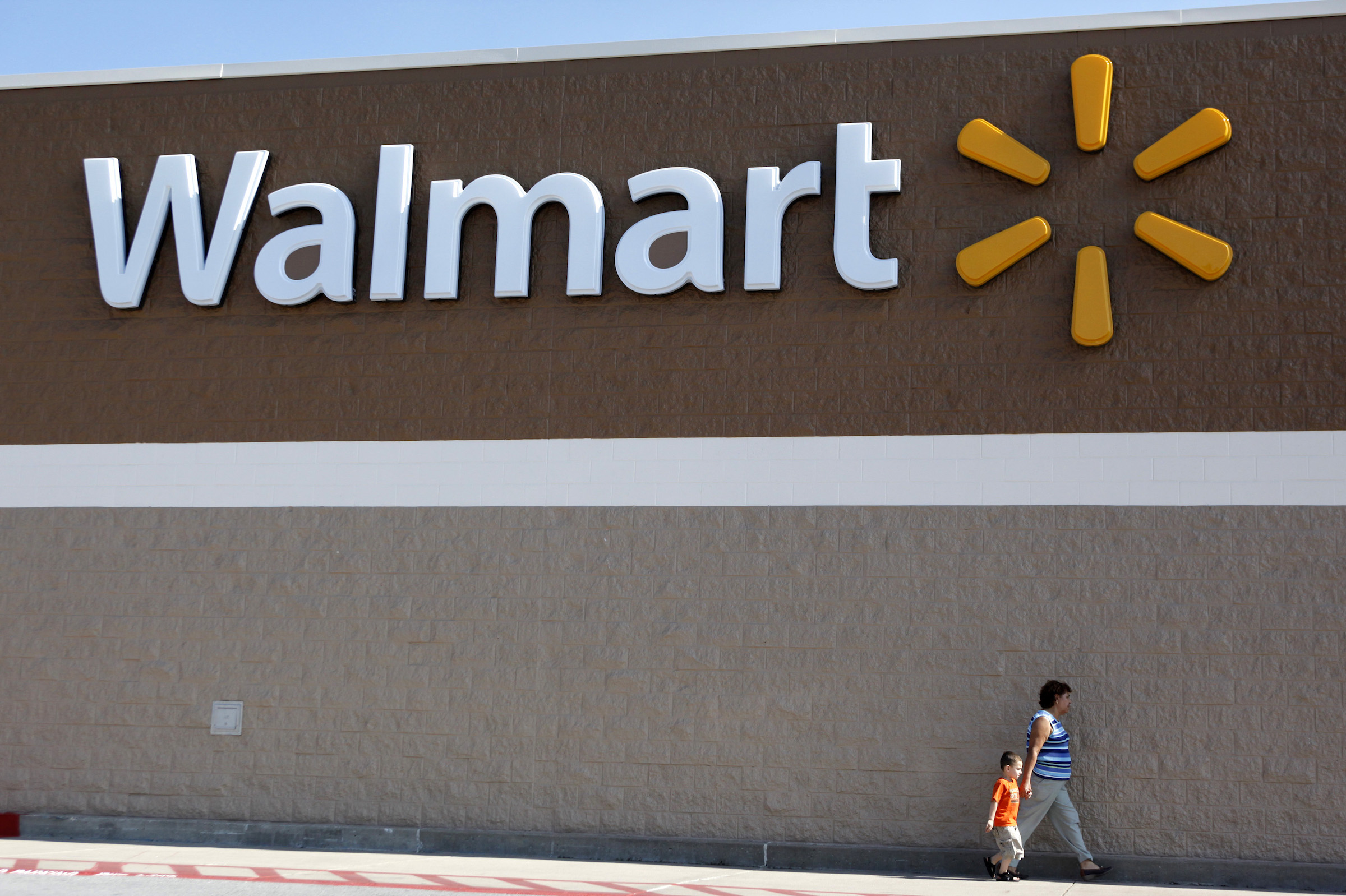 People walk past a Wal-Mart sign in Rogers, Arkansas June 4, 2009. Wal-Mart Stores Inc said on Thursday that its strong financial position leaves it well positioned to take advantage of acquisition opportunities across the globe.
