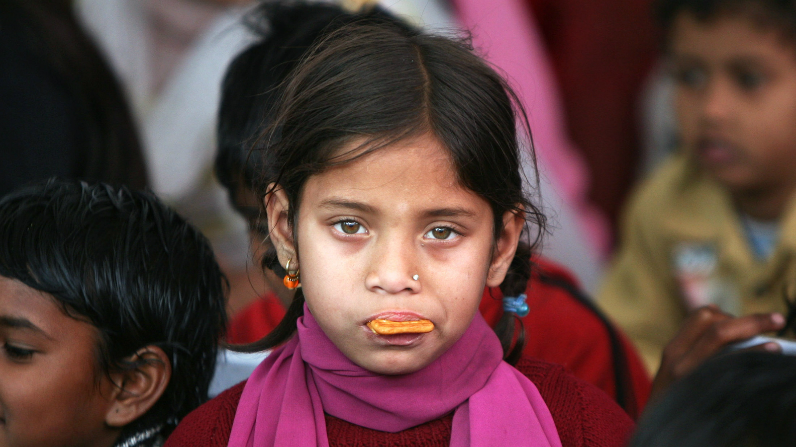 A rescued child labourer eats a biscuit during a protest march in New Delhi February 17, 2010. Hundreds of rescued labourers on Wednesday participated in the march demanding the government to allocate 6 percent of the country's GDP on education and to avoid privatisation of education, according to the organizers.