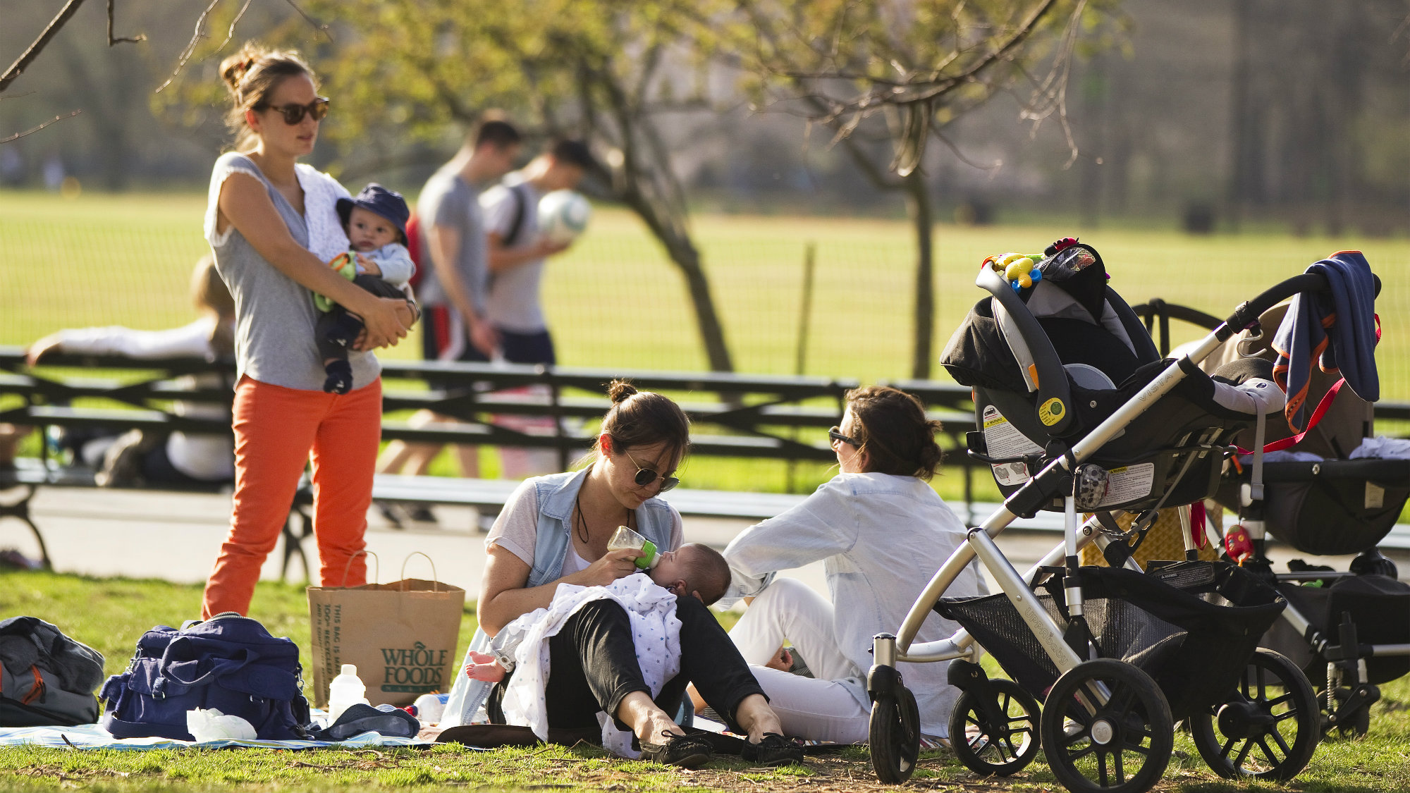 Mothers relax on the grass with their babies at Central Park during a warm day in New York