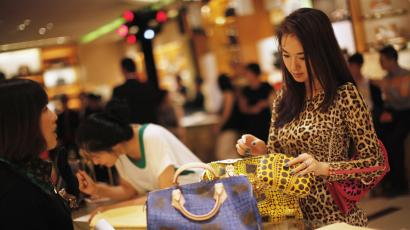 A woman shops in a Louis Vuitton store during Vogue's 4th Fashion's Night Out: Shopping Night with Celebrities in downtown Shanghai September 7, 2012.