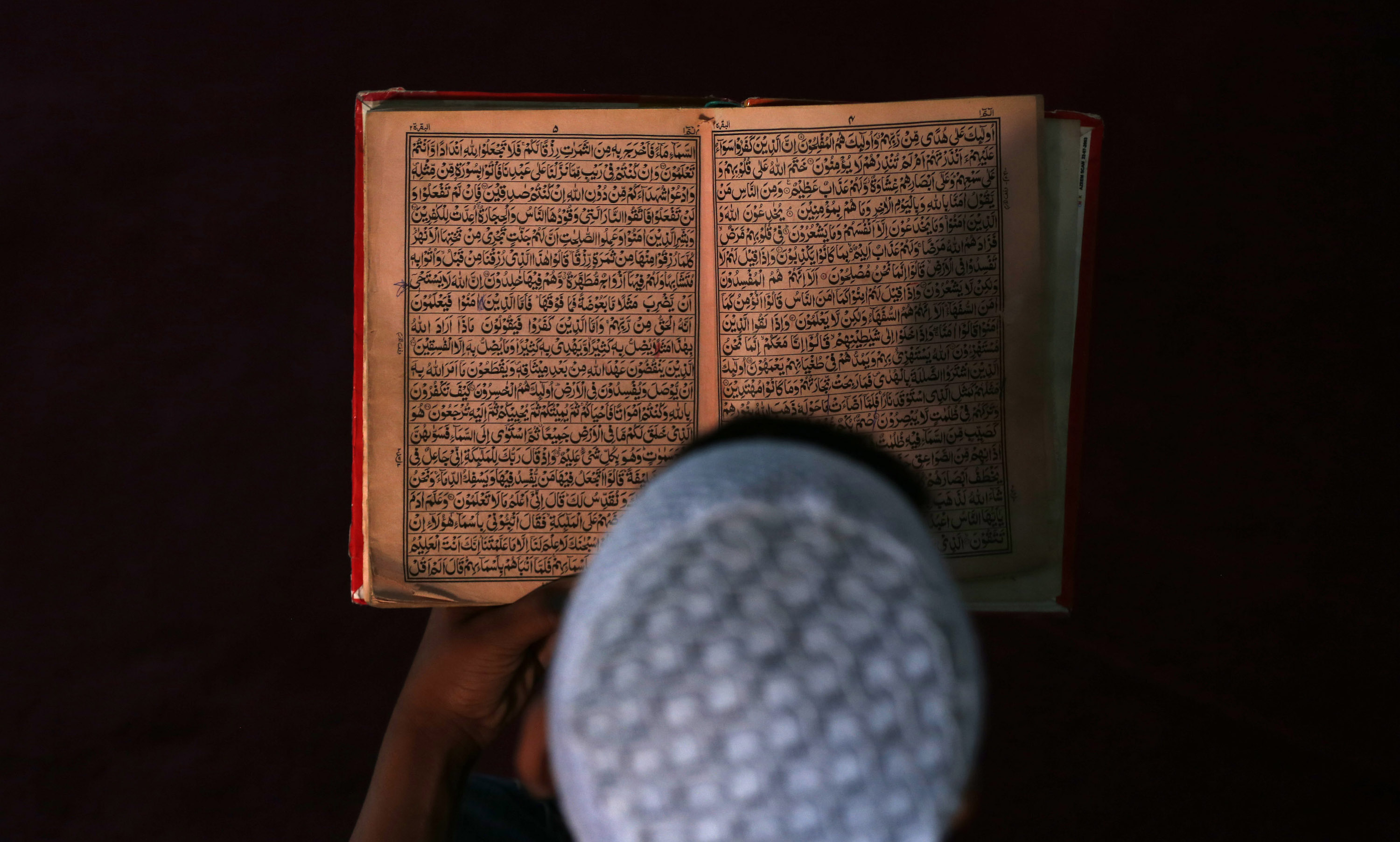 An Afghan boy reads the Koran in a madrasa, or religious school, during the Muslim holy month of Ramadan in Kabul June 30, 2014. REUTERS/Mohammad Ismail (AFGHANISTAN - Tags: RELIGION TPX IMAGES OF THE DAY EDUCATION SOCIETY) - RTR3WGFF