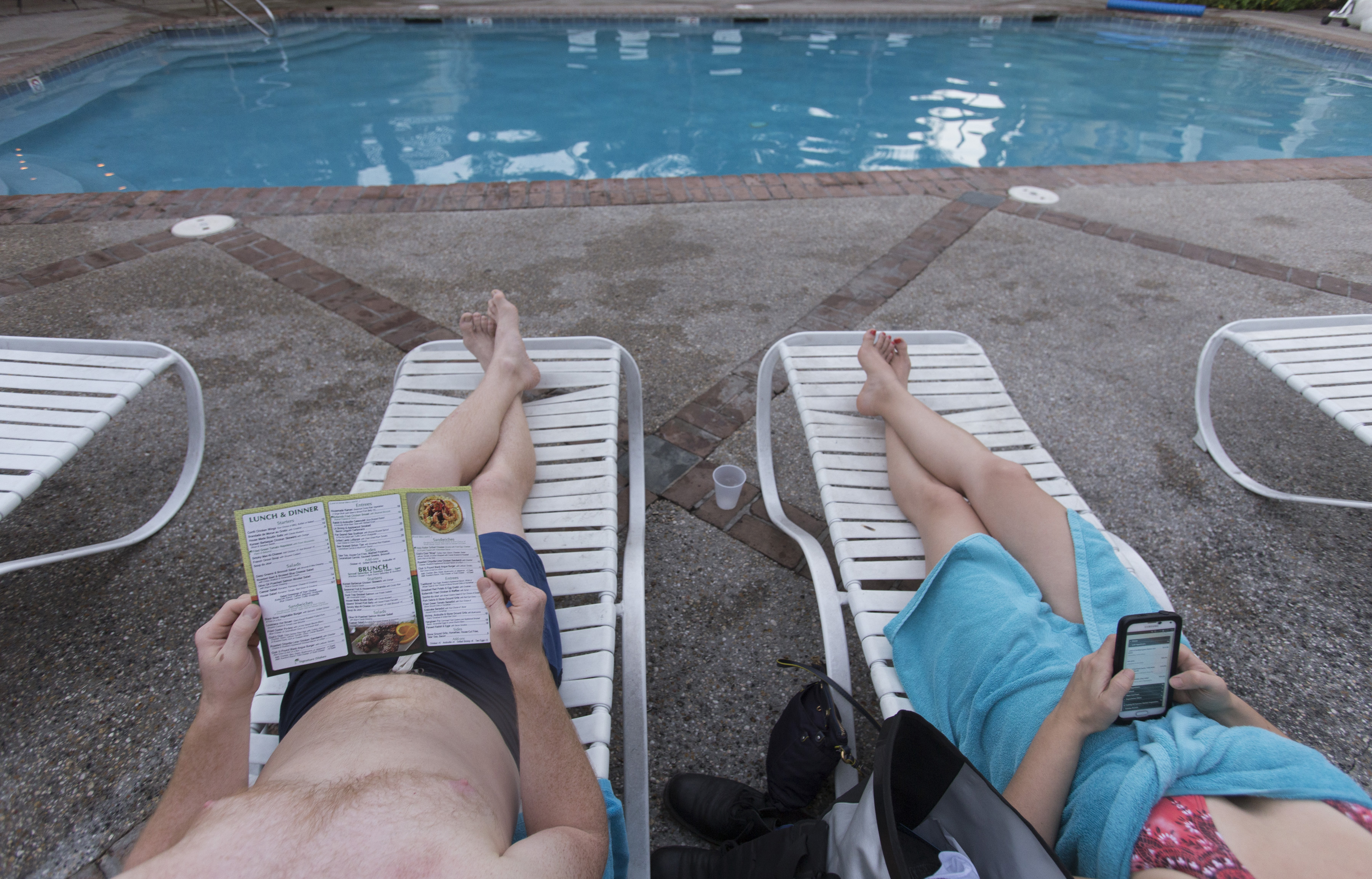 A couple lounges on deck chairs by the pool at the Country Club in New Orleans