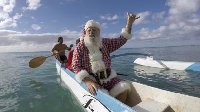 Donald Boyce, dressed up like Santa Claus, waves to surfers as he goes outrigger canoe surfing off Waikiki beach in Honolulu, Hawaii December 13, 2014.