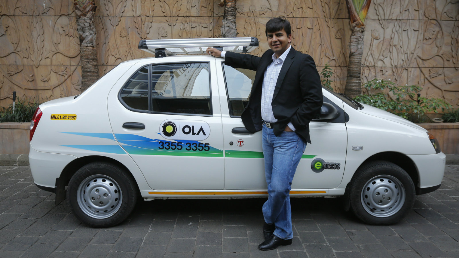Bhavish Aggarwal, CEO and co-founder of Ola, an app-based cab service provider, poses in front of an Ola cab in Mumbai March 3, 2015. Ola, India's largest online taxi business, will more than double its reach by expanding into 200 cities after this week's acquisition of rival TaxiForSure handed it control of more than 80 percent of the country's organised cab market. The company aims to capitalise on India's low level car ownership, with urbanites deterred by both the expense and the lack of parking space, its 29-year-old Chief Executive Aggarwal told Reuters on Tuesday.