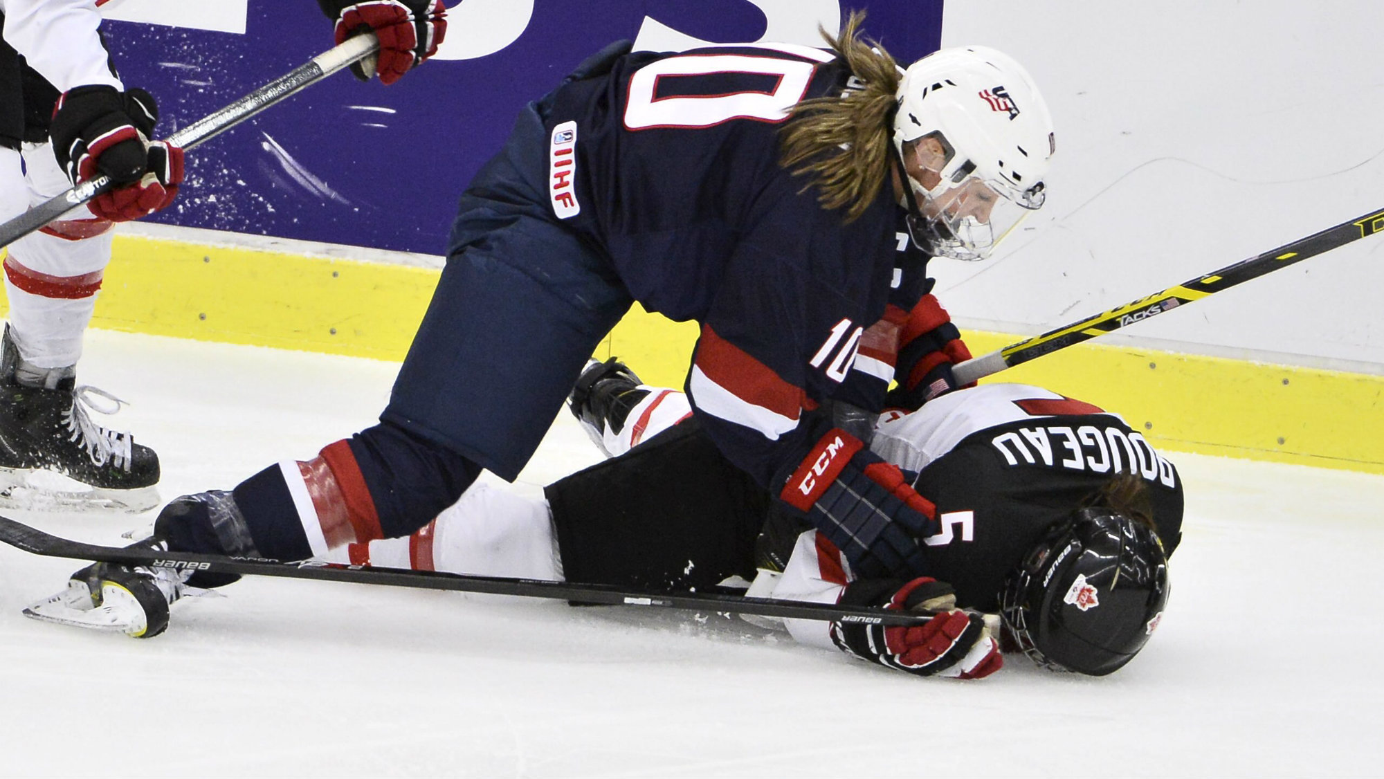 Megan Duggan of the U.S. fights for the puck with Canada's Lauriane Rougeau on the ice during the 2015 IIHF Ice Hockey Women's World Championship gold medal match between USA and Canada at Malmo Isstadion in Malmo, southern Sweden, April 4, 2015. /TT News Agency