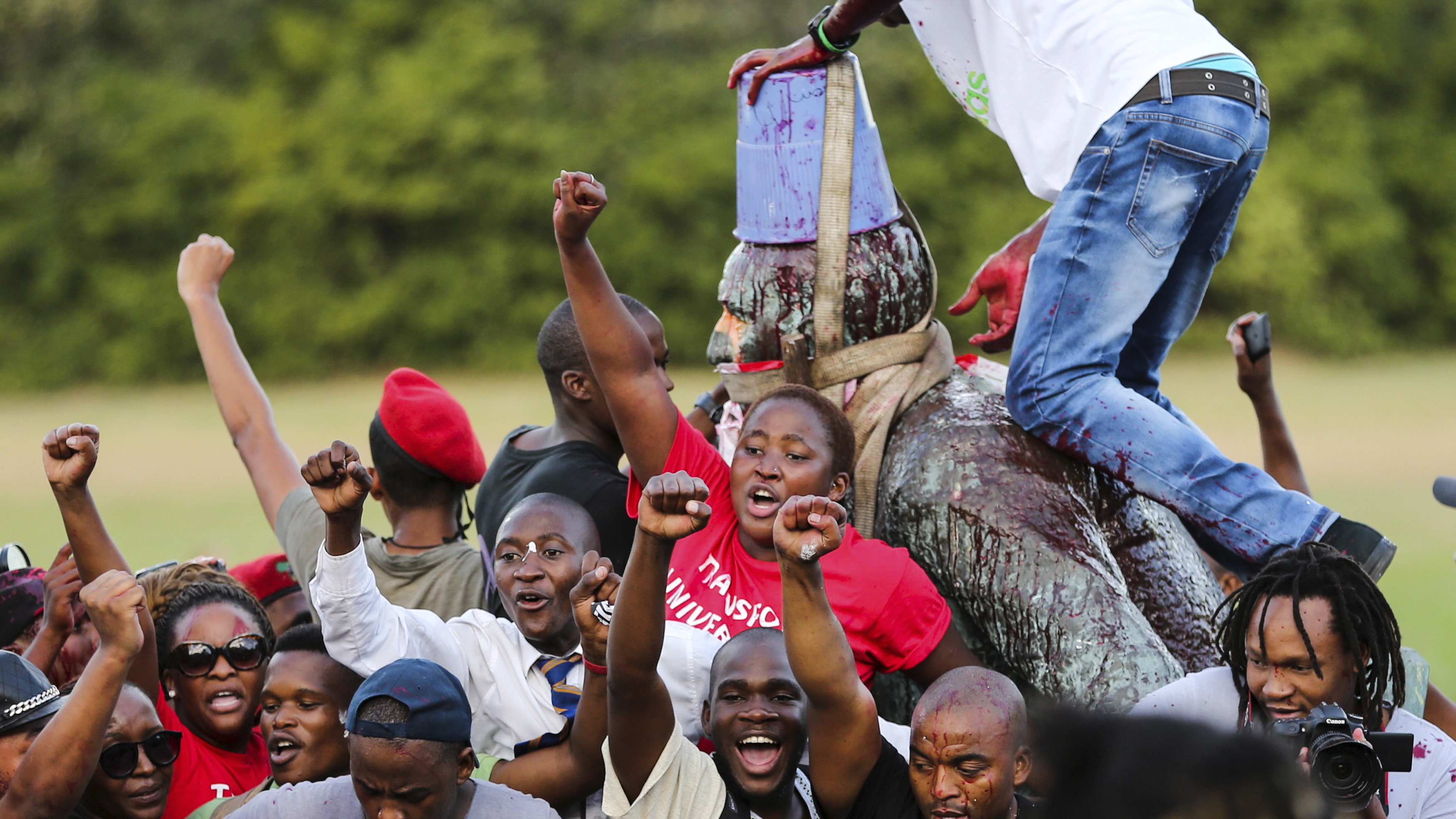 Students cheer as the statue of  Cecil John Rhodes is removed from the University of Cape Town (UCT), April 9, 2015. The statue at the university, one of Africa's top academic institutions, has been covered up for the past few weeks as both white and black students regularly marched past with #Rhodesmustfall placards calling for its removal. They believe it is a symbol of the racism against blacks that prevails in South Africa two decades after the end of oppressive white-minority rule. REUTERS/Sumaya Hisham      TPX IMAGES OF THE DAY      - RTR4WPIR