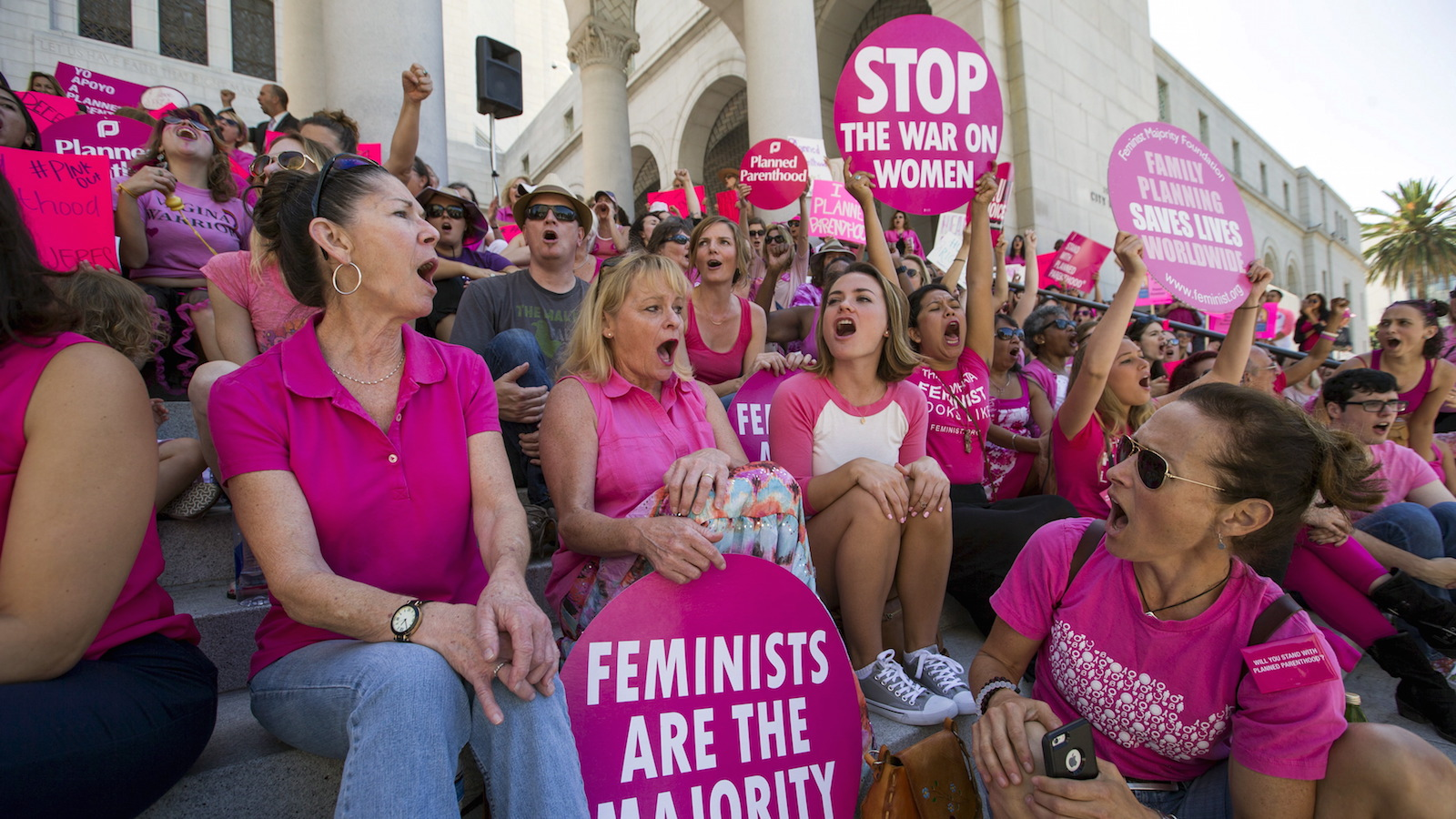 """Activists chant as they rally in support of Planned Parenthood on """"National Pink Out Day"""" on the steps of City Hall in Los Angeles, California September 29, 2015. U.S. Congressional Republicans on Tuesday challenged Planned Parenthood's eligibility for federal funds, while the health organization's president said defunding it would restrict women's access to care and disproportionately hurt low-income patients. REUTERS/Mario Anzuoni - RTS2C4S"""