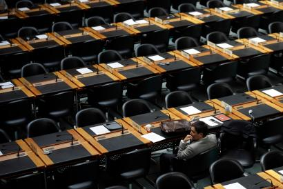 A delegate waits for the opening of a session of the Trade Negotiation Committee at the World Trade Organization (WTO) in Geneva July 22, 2013.