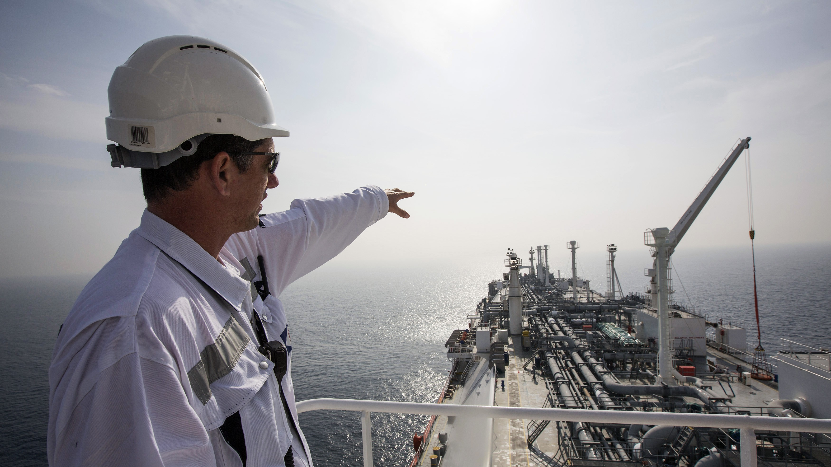 """An officer points as he stands on a tanker carrying liquefied natural gas in the Mediterranean, some 10 km (6 miles) from the coastal Israeli city of Hadera January 22, 2014. Permanently anchored in the choppy waters of the eastern Mediterranean, the tanker Excellence is in a constant state of alert, waiting for the emergency phone call that Israel needs fuel. The gas, imported and stored in liquid form on the tanker, can be """"regassified"""" and pumped through a special buoy into an underwater pipeline, providing the Israeli Electric Corp its auxiliary supplies. Picture taken January 22, 2014. REUTERS/Baz Ratner (ISRAEL - Tags: ENERGY BUSINESS) - RTX181TU"""