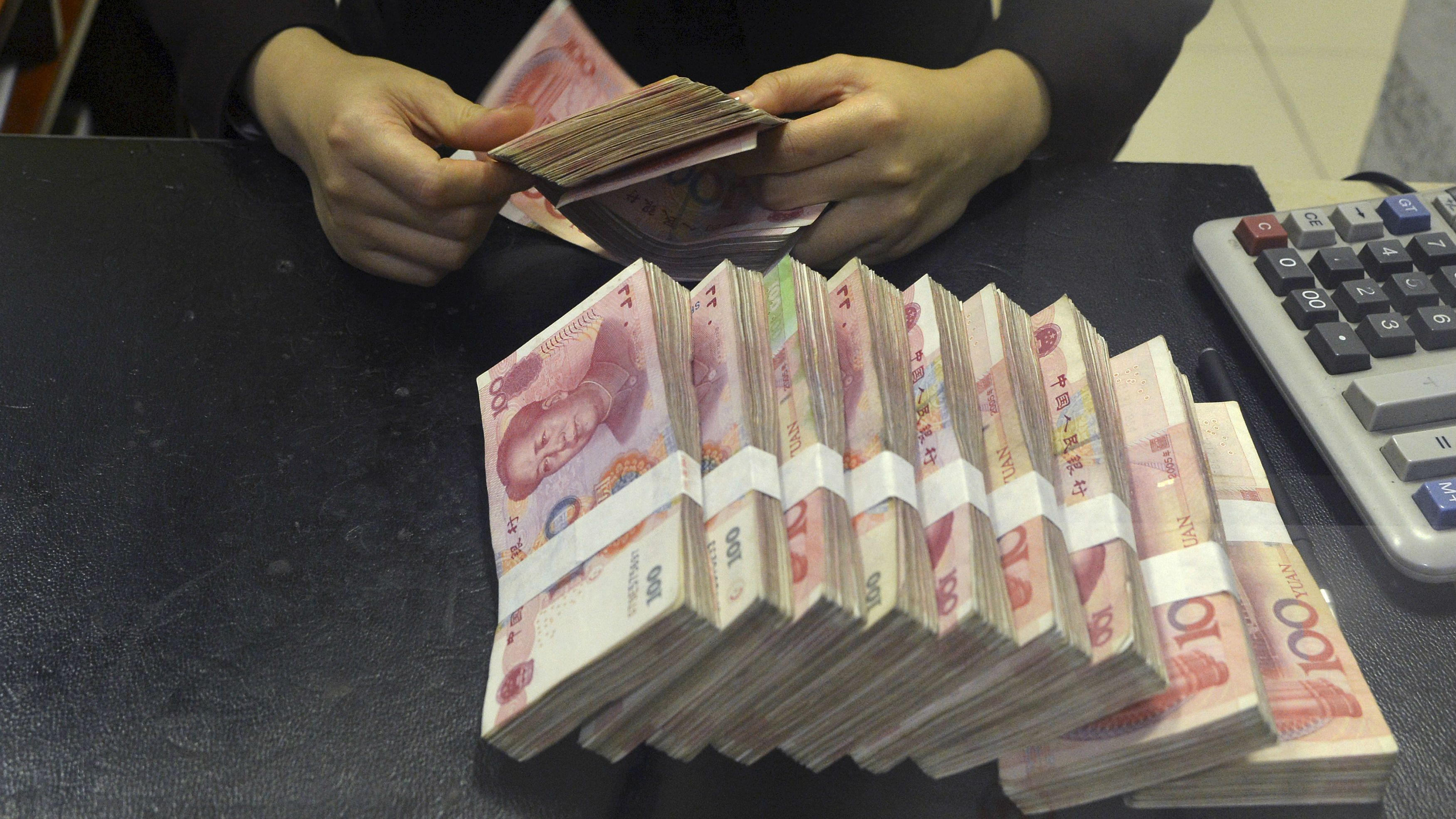 A clerk counts 100 Chinese yuan banknotes at a branch of China Merchants Bank in Hefei, Anhui province April 20, 2015. China's central bank on Sunday cut the amount of cash that banks must hold as reserves, the second industry-wide cut in two months, adding more liquidity to the world's second-biggest economy to help spur bank lending and combat slowing growth. REUTERS/Stringer