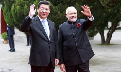 Chinese President Xi Jinping (L) and Indian Prime Minister Narendra Modi wave as they visit Dacien Buddhist Temple in Xian, Shaanxi province, China, May 14, 2015. REUTERS/China Daily CHINA OUT. NO COMMERCIAL OR EDITORIAL SALES IN CHINA - RTX1CZ3F