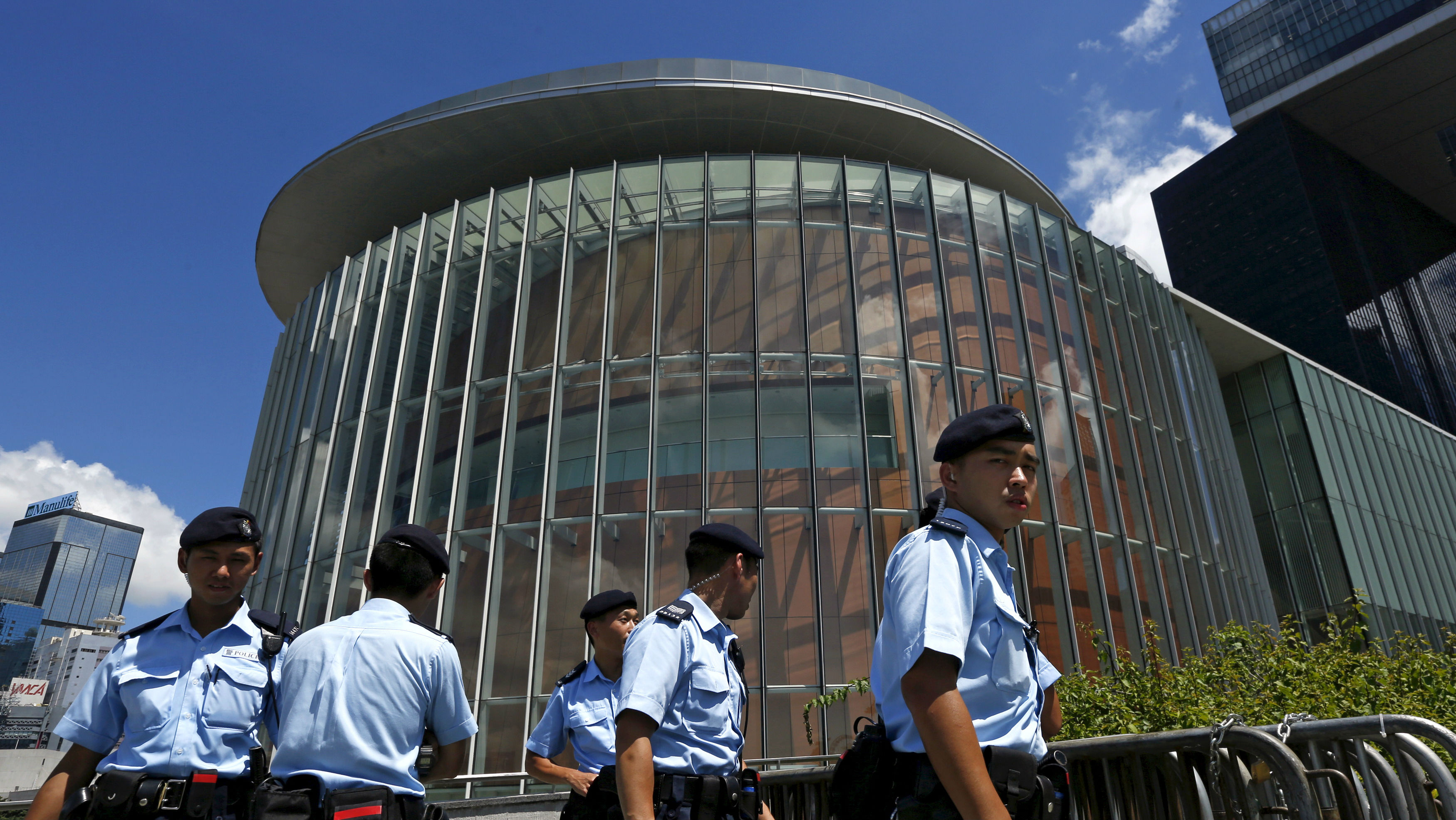 Policemen patrol outside the Legislative Council building in Hong Kong, China June 15, 2015. Hong Kong is gearing up for a vote this week on a contentious electoral reform package backed by Beijing, with a weekend poll showing public support has shifted against the proposal amid renewed street marches by pro-democracy protesters. REUTERS/Bobby Yip