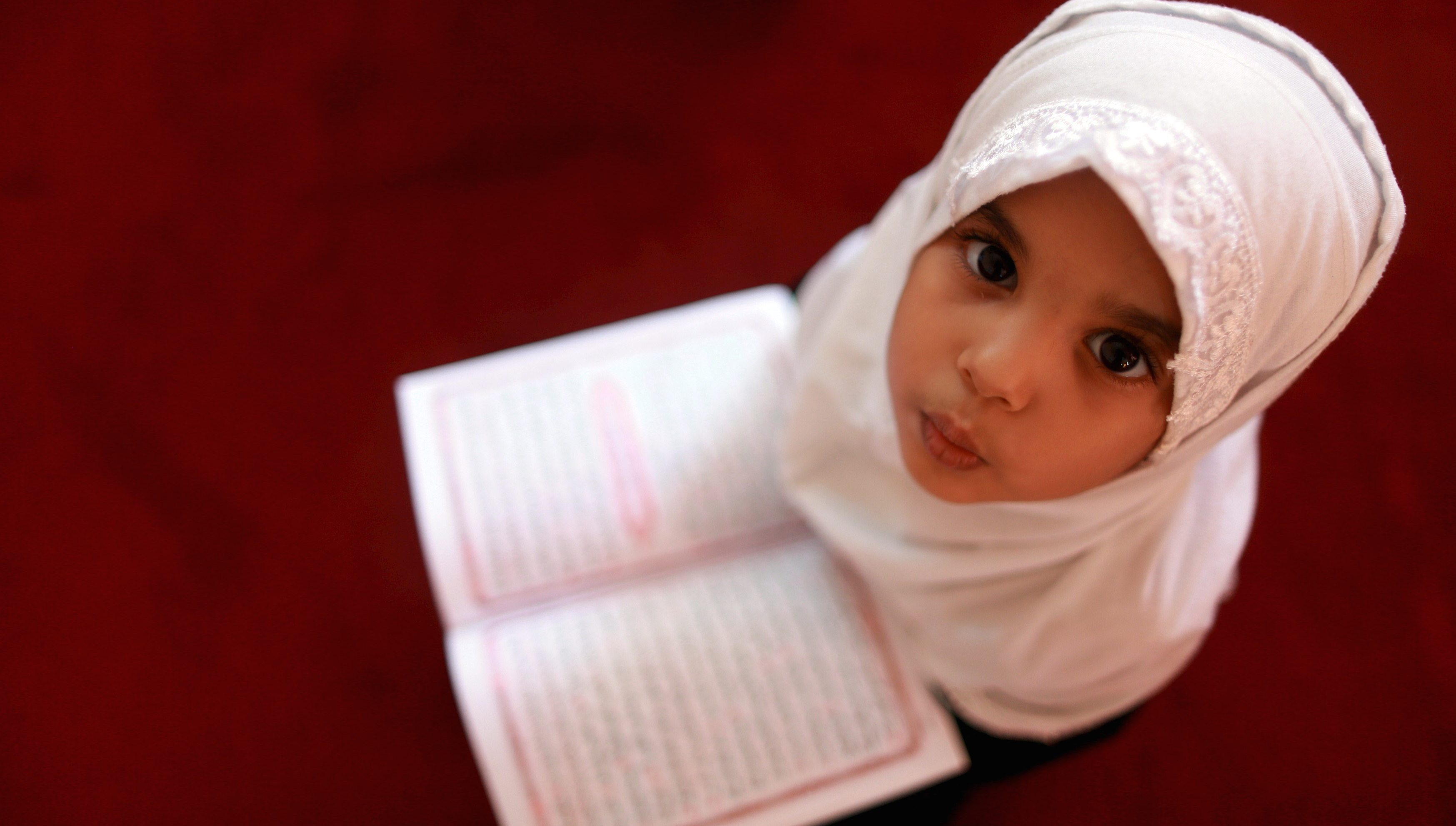 A girl reads the Koran at a Koranic school during the Muslim holy fasting month of Ramadan, in Benghazi