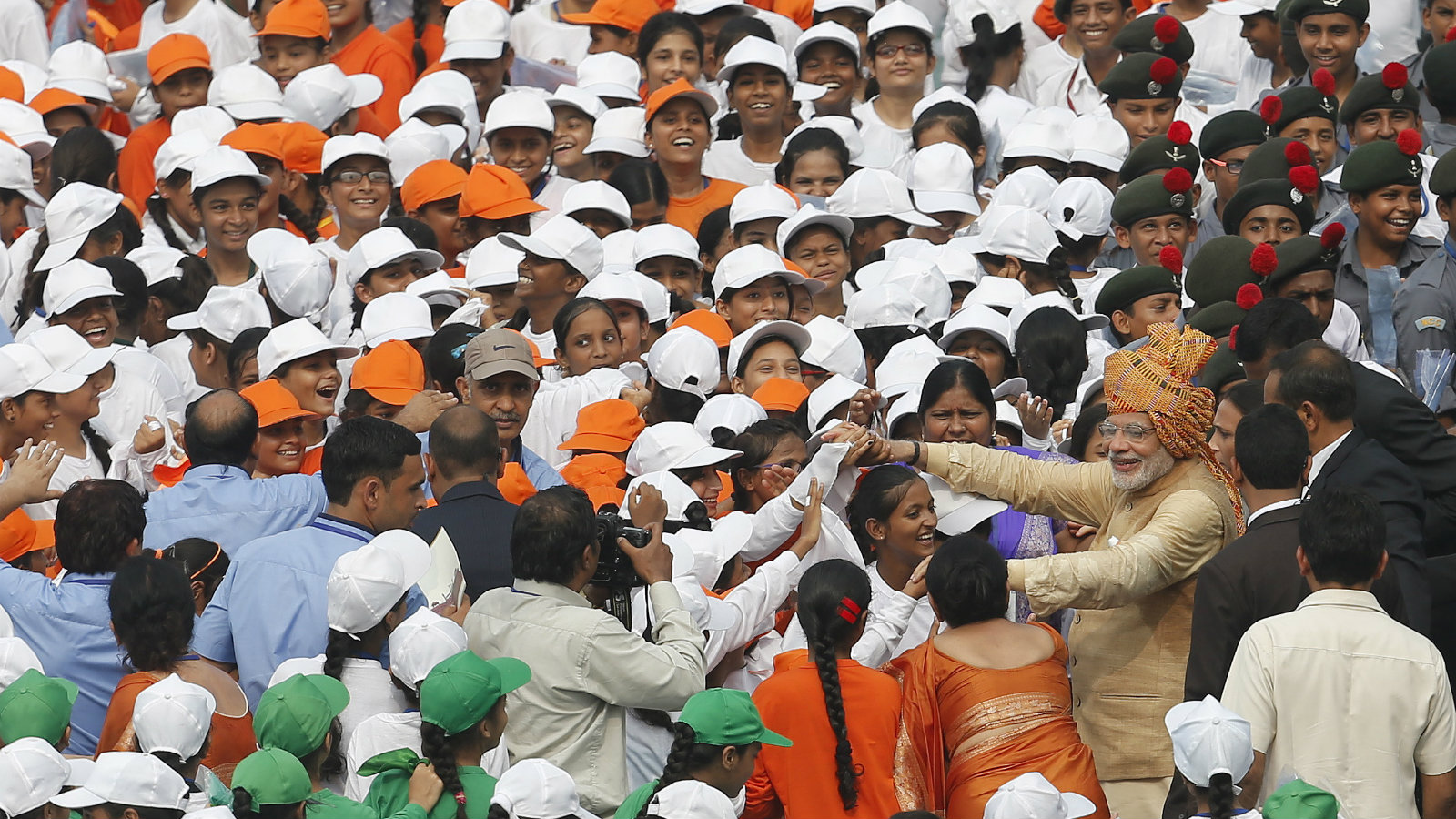 Indian Prime Minister Narendra Modi (R, wearing turban) greets school children after addressing the nation from the historic Red Fort during Independence Day celebrations in Delhi, India, August 15, 2015. Modi sought to shed an image that he governs for big business on Saturday, vowing to help the poor in an annual speech aimed at bolstering popularity rather than tackling setbacks to his economic reform plans.