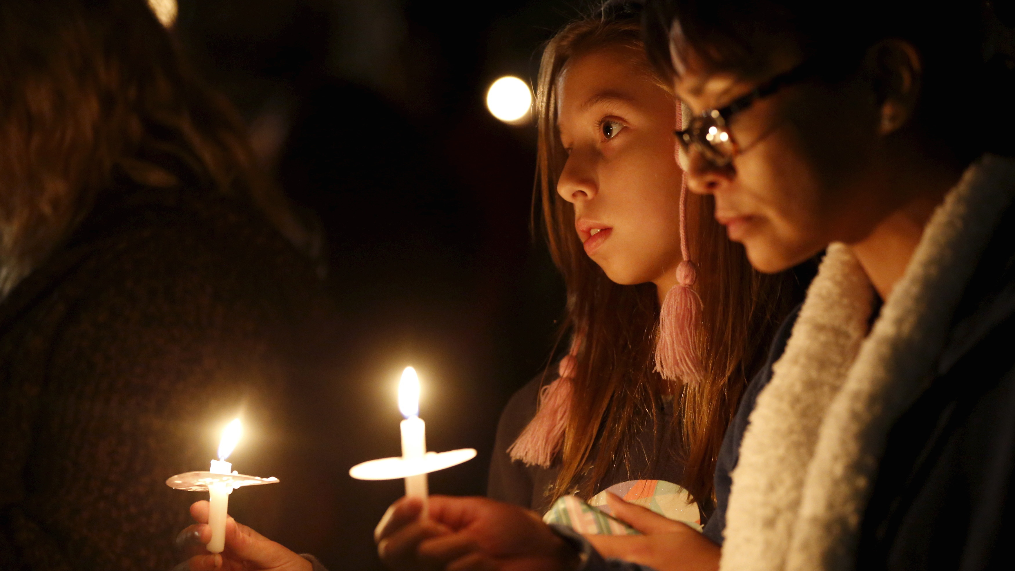 Attendees reflect on the tragedy of Wednesday's attack during a candlelight vigil in San Bernardino, California December 3, 2015. California shooter Syed Rizwan Farook, 28, and Tashfeen Malik, 27, his wife and mother of his 6-month-old daughter, were killed in a shootout with police after the couple opened fire at the Inland Regional Center social services agency in the city of San Bernardino, killing 14 people.   REUTERS/Mario Anzuoni  - RTX1X40A