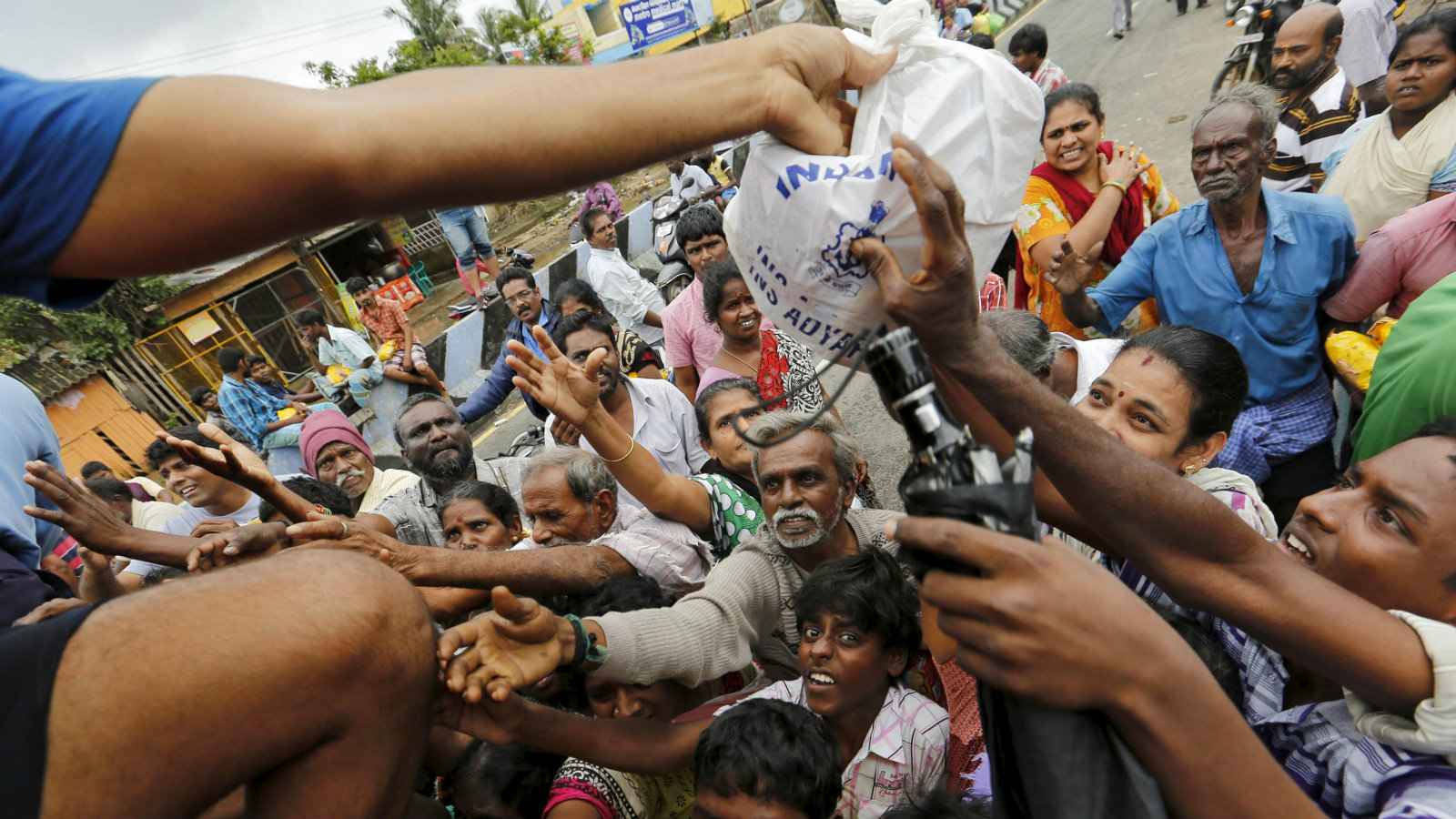 Flood-affected people raise their hands to receive free food being distributed by Indian Navy personnel in Chennai, India, December 5, 2015.