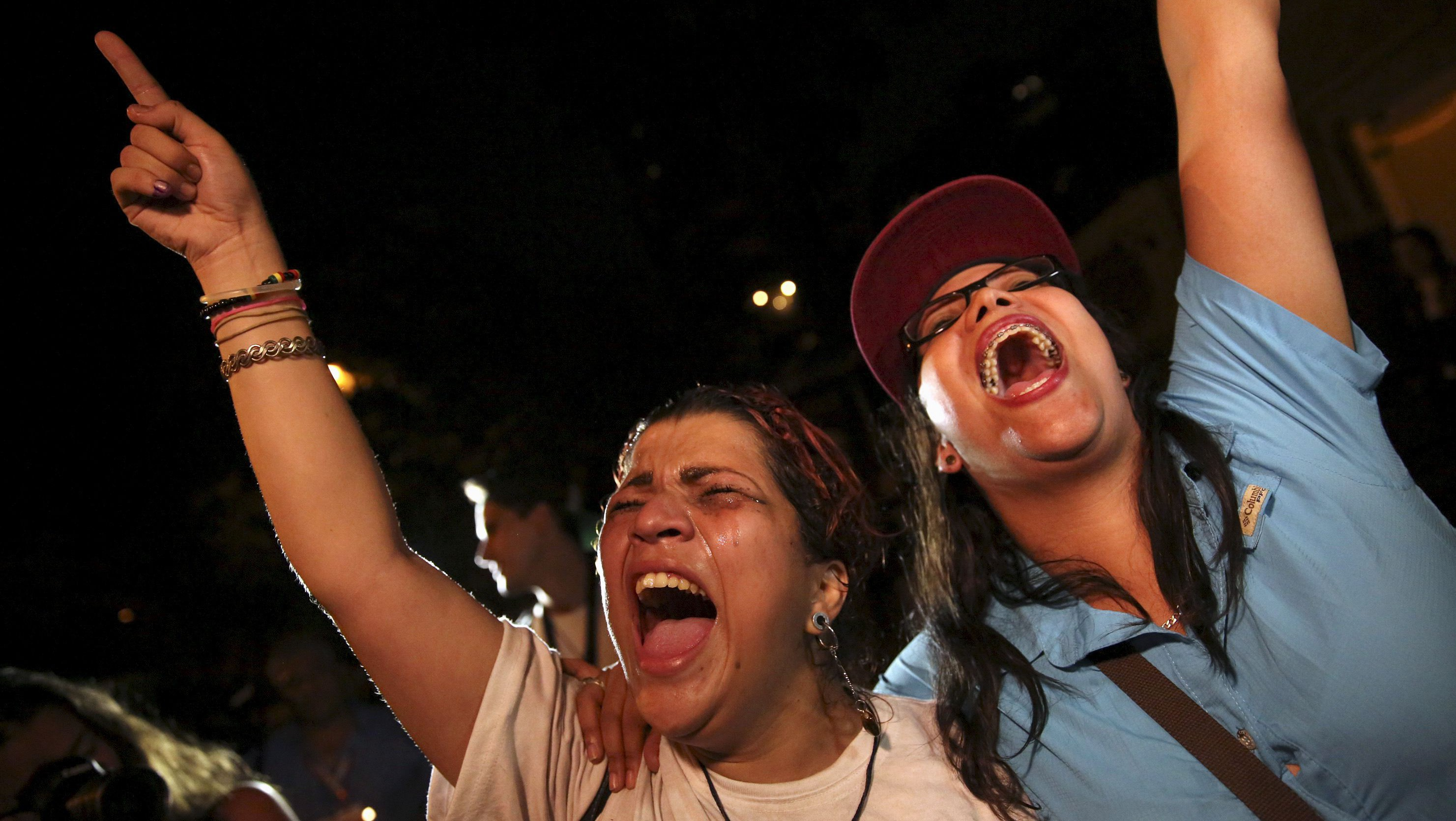 Opposition supporters shout while they celebrate their victory on a street in Caracas