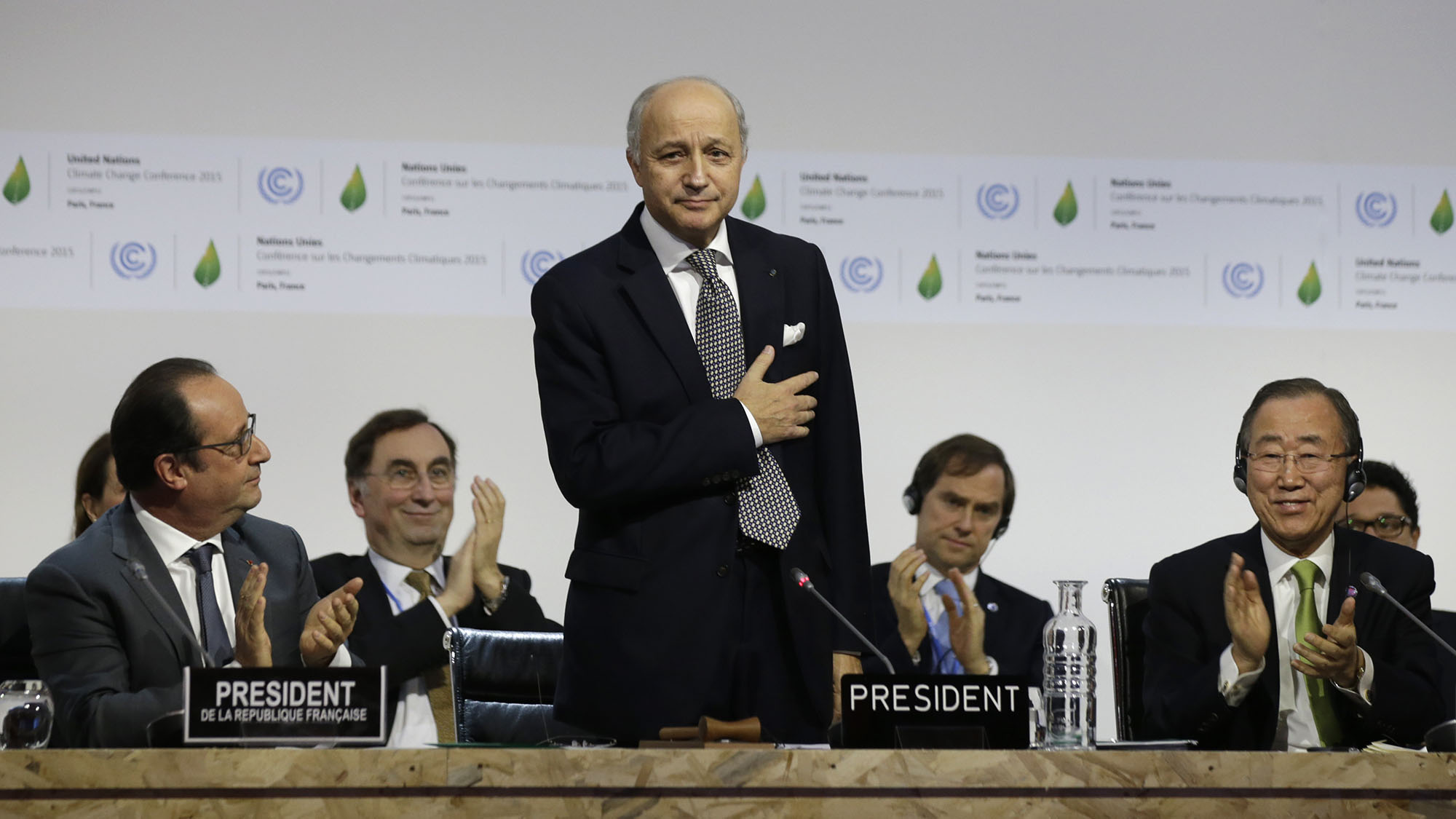 French Foreign Affairs Minister Laurent Fabius (C), President-designate of COP21, puts his hand over his heart after his speech as he stands near French President Francois Hollande (L) and United Nations Secretary-General Ban Ki-moon (R) at the World Climate Change Conference 2015 (COP21) at Le Bourget, near Paris, France, December 12, 2015.             TPX IMAGES OF THE DAY  - RTX1YCFS