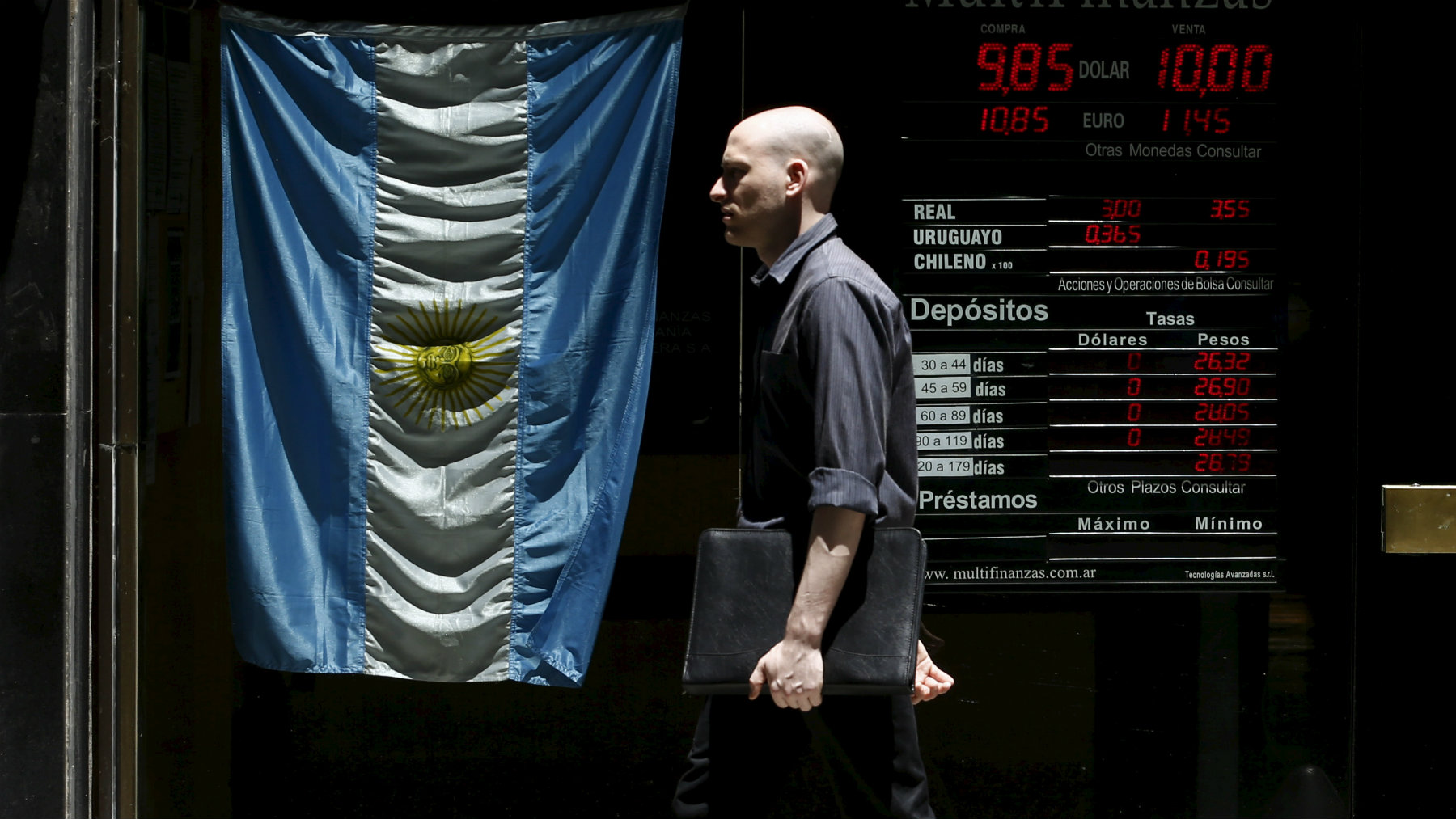 A man walks past a currency exchange rates board at a money exchange in Buenos Aires' financial district.
