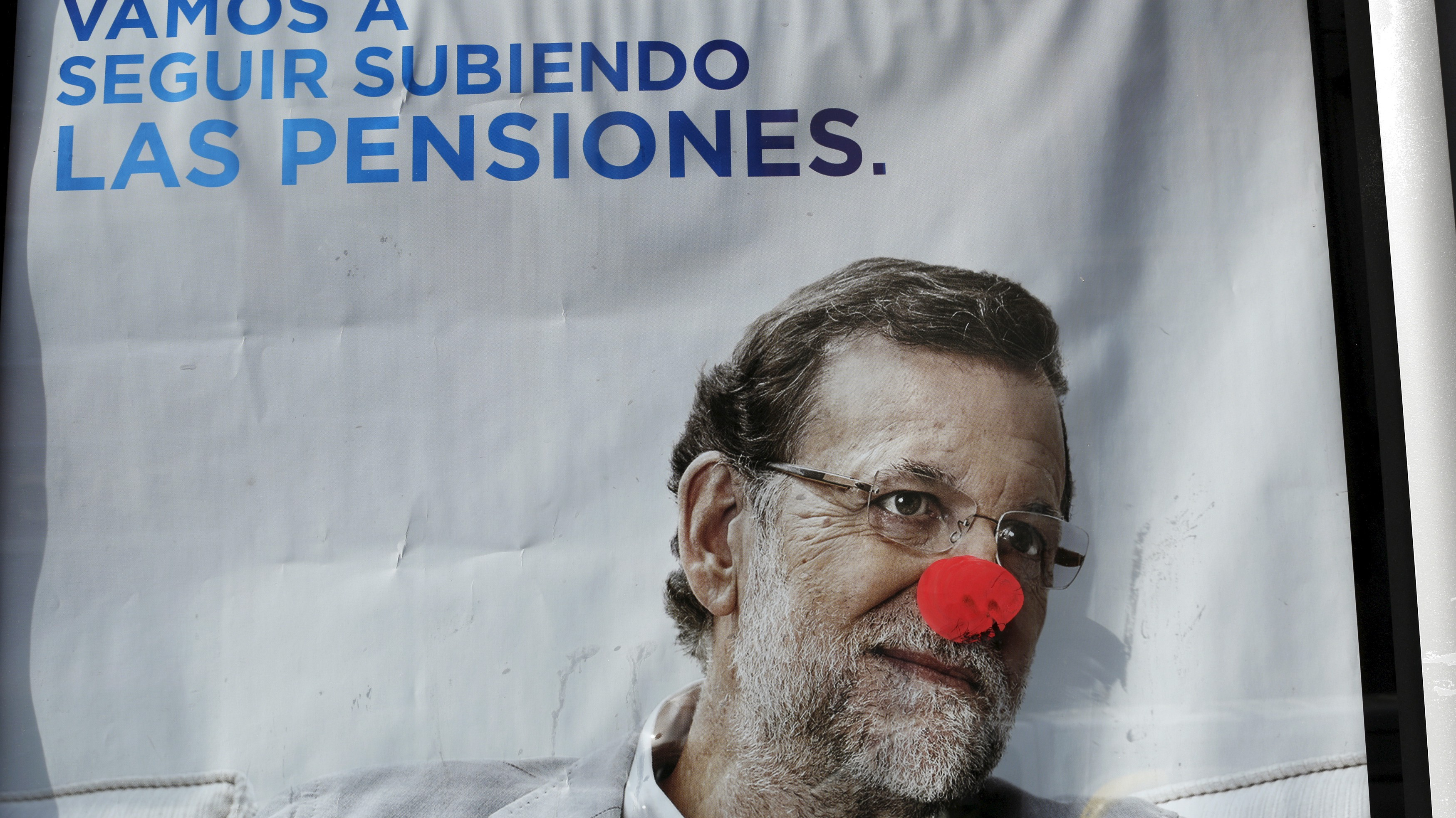 A defaced campaign poster of Spanish Prime Minister and ruling People's Party (PP) leader Mariano Rajoy, one of the four leading candidates for Spain's general election, is pictured in Seville, southern Spain December 16, 2015.