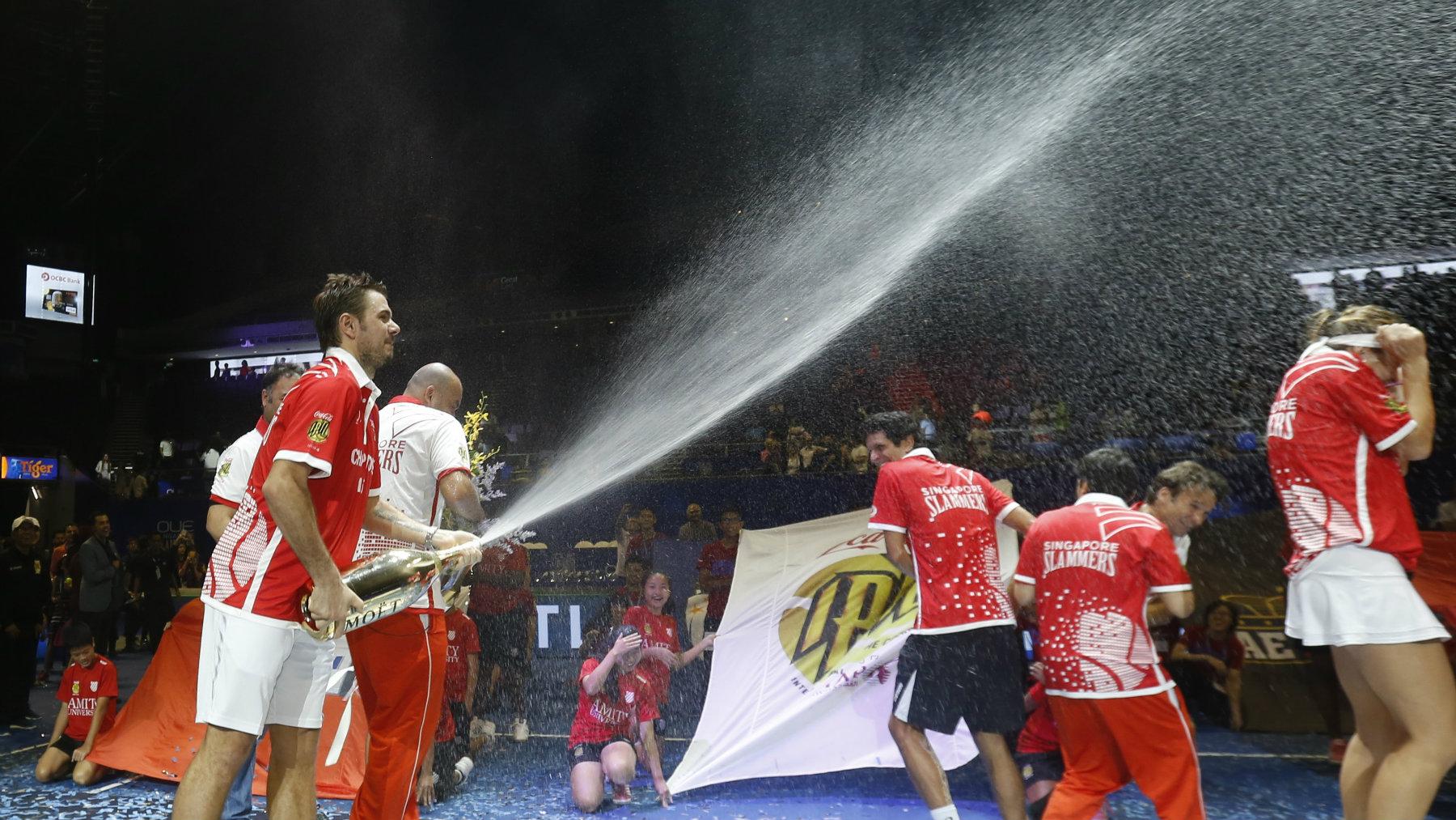 International Premier Tennis League Final Stan Wawrinka sprays champagne with members of the Singapore Slammers after winning the final.