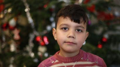 Seven-year old Karam of Syria poses in front of a Christmas tree at a refugee shelter in an evangelic church in Oberhausen, Germany, December 22, 2015