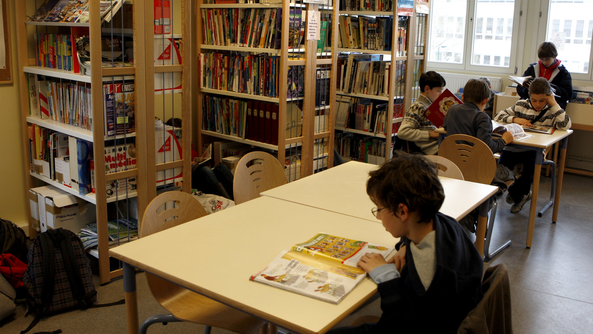 Children read books in the library of a school in Vincennes