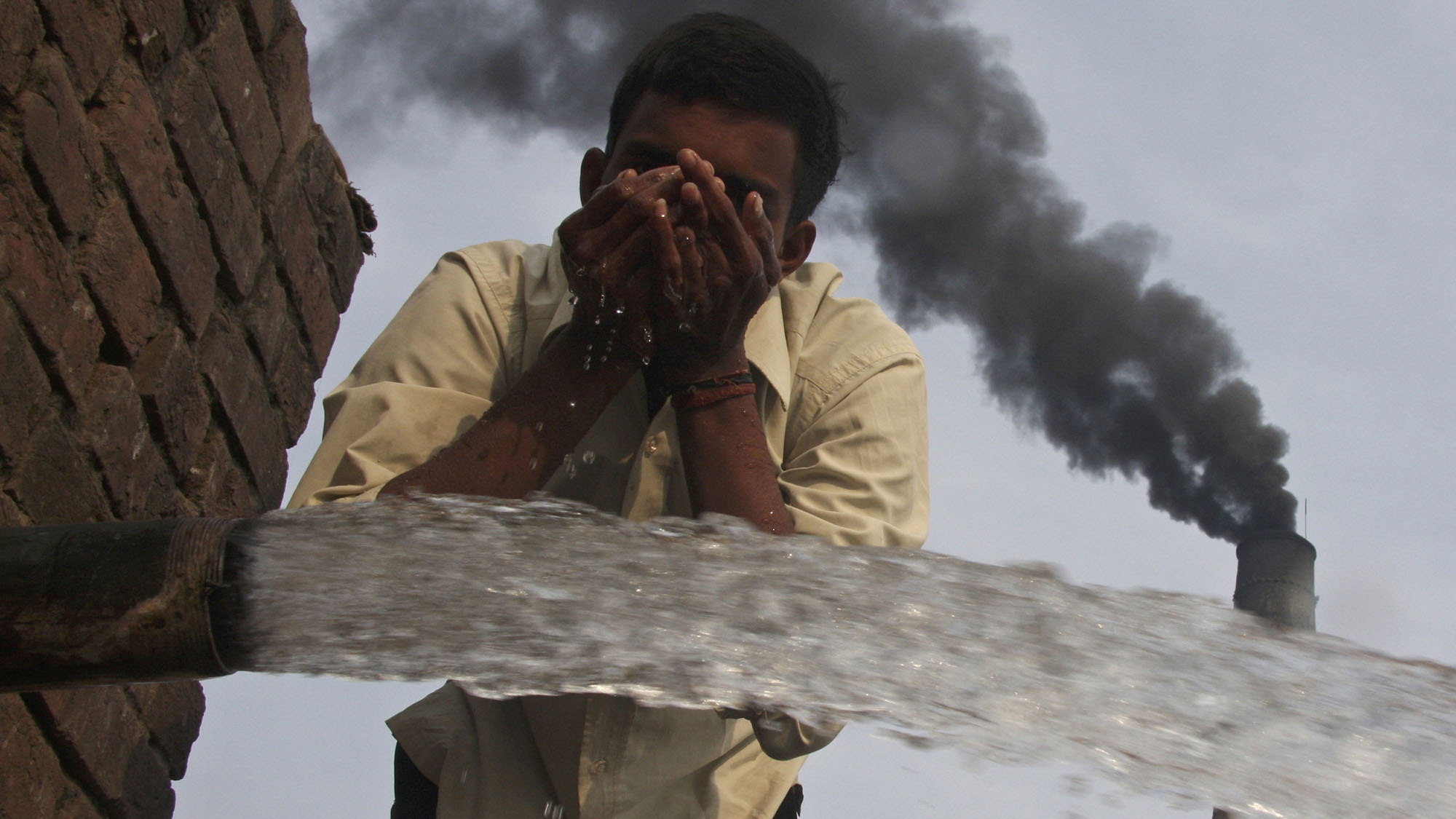 A labourer drinks water as smokes rise from a chimney of a brick factory at Togga village on the outskirts of the northern Indian city of Chandigarh December 6, 2009. India set a goal on Thursday for slowing the growth of its greenhouse gas emissions, the last major economy to offer a climate target four days before the start of U.N. talks on combating global warming.