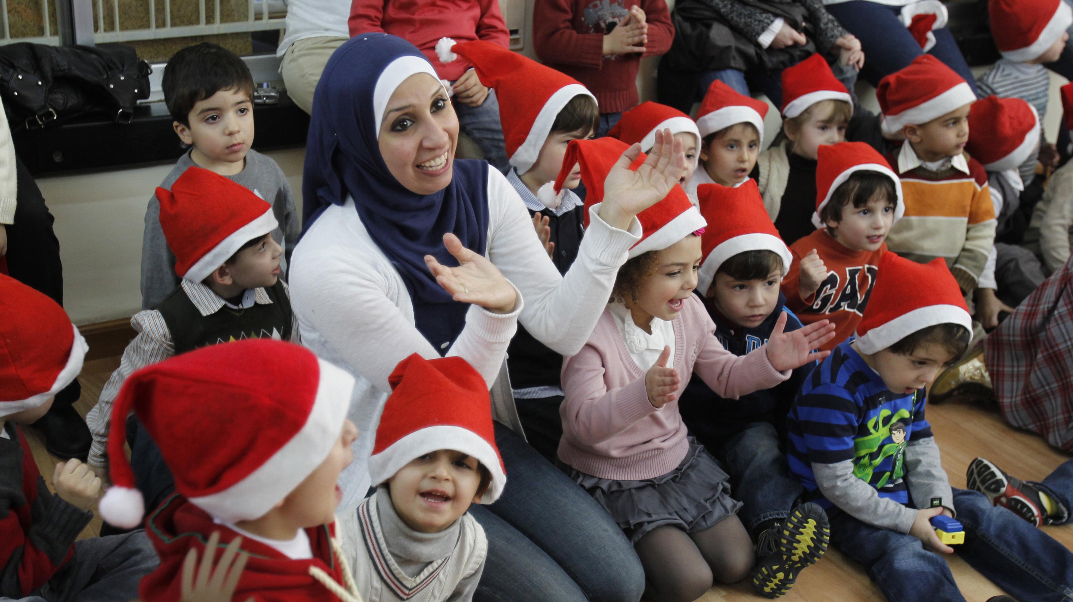 Muslim and Christian schoolchildren wear Santa hats in Amman