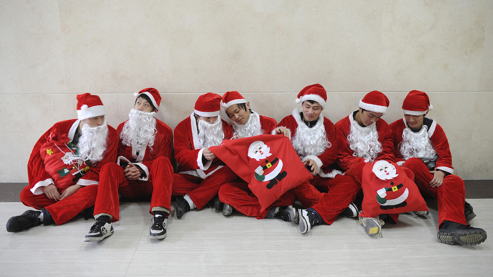 Workers dressed as Santa Claus to celebrate the upcoming Christmas Day, rest at a shopping mall in Hefei
