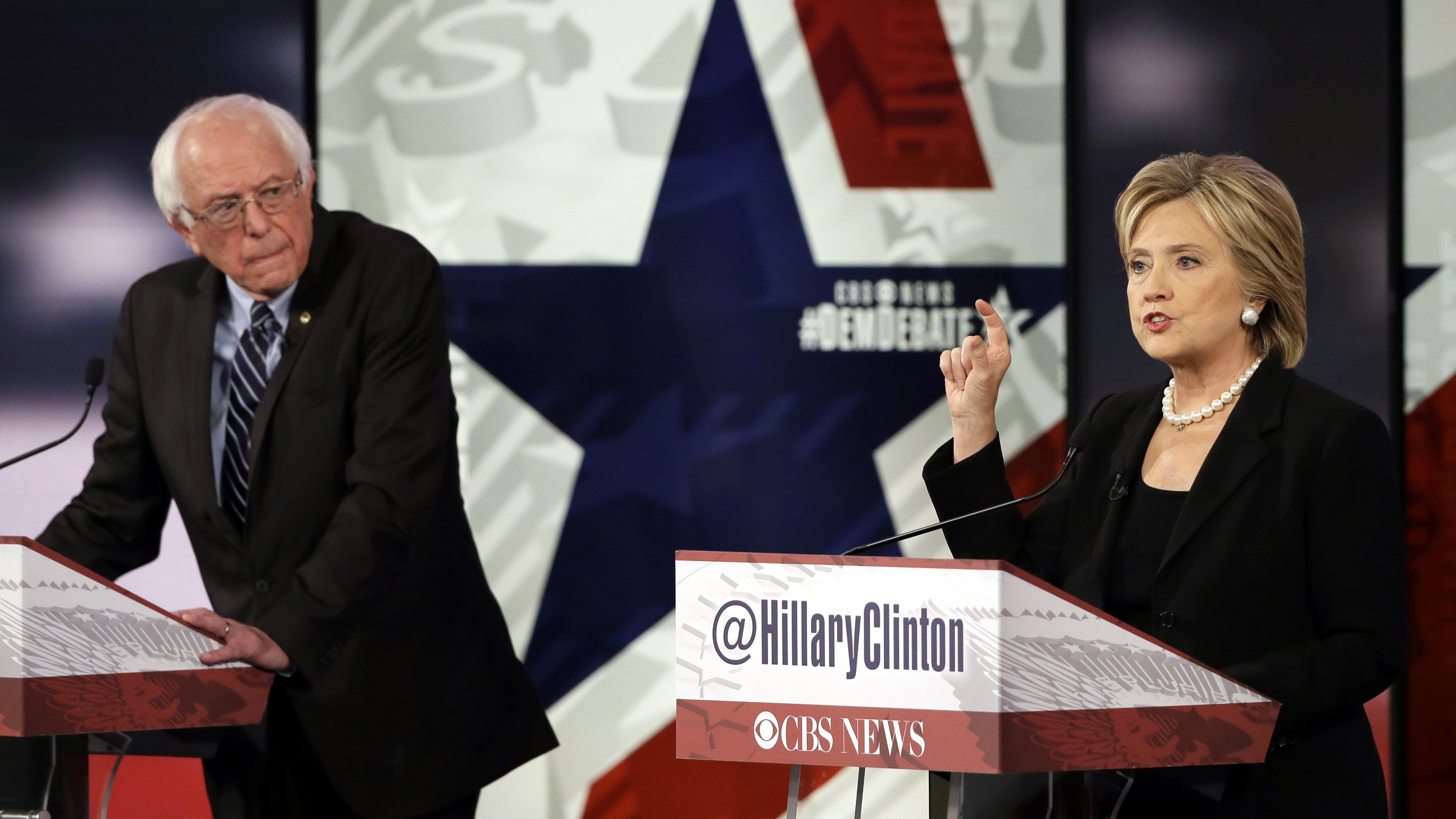 In this Nov. 14, 2015, photo, Hillary Rodham Clinton, right, makes a point as Bernie Sanders listens during a Democratic presidential primary debate in Des Moines, Iowa. Clinton and Sanders are outlining the steps on Nov. 19, they would take to combat the Islamic State group, each making major speeches less than a week after the deadly attacks in Paris.