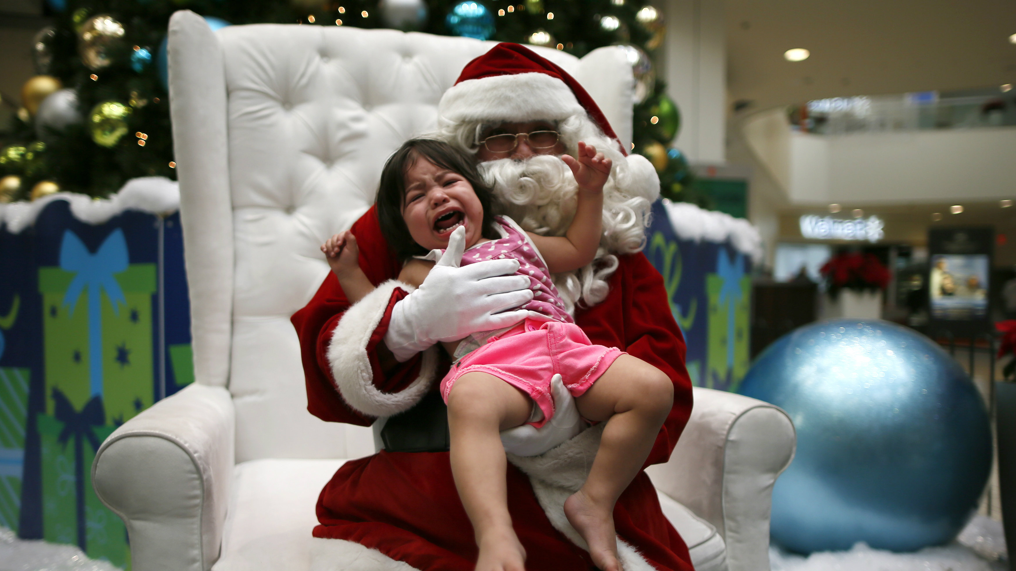 Latino Santa Claus Mario Vasquez, who is from Honduras, poses with one-year-old Hailey Chinchilla at Baldwin Hills Crenshaw Plaza mall in Los Angeles, California, December 16, 2013. A New Mexico teacher who told an African American student that Santa Claus was white has been put on paid administrative leave, an official said on Monday. REUTERS/Lucy Nicholson