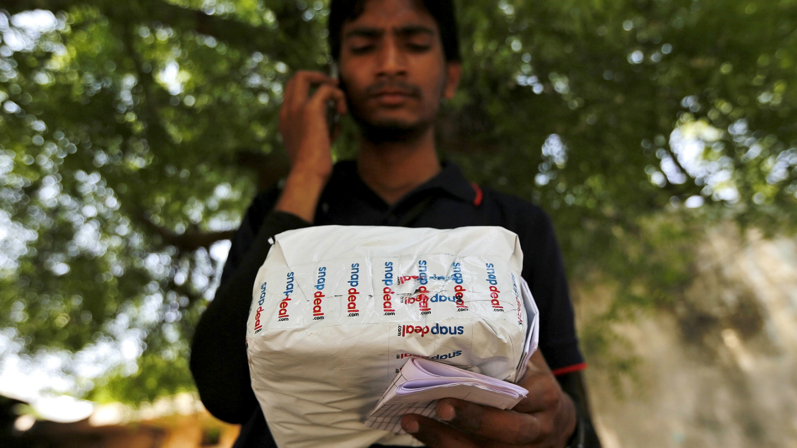 A worker of Indian e-commerce company Snapdeal.com makes a call to a customer before delivering a packet in Ahmedabad, India, April 17, 2015. After losing top engineering talent for years to America's tech heartland of Silicon Valley, India is luring them back as an e-commerce boom sparks a thriving start-up culture, unprecedented pay, and perks including free healthcare for in-laws. Picture taken April 17, 2015. To match INDIA-ECOMMERCE/WORKERS. REUTERS/Amit Dave