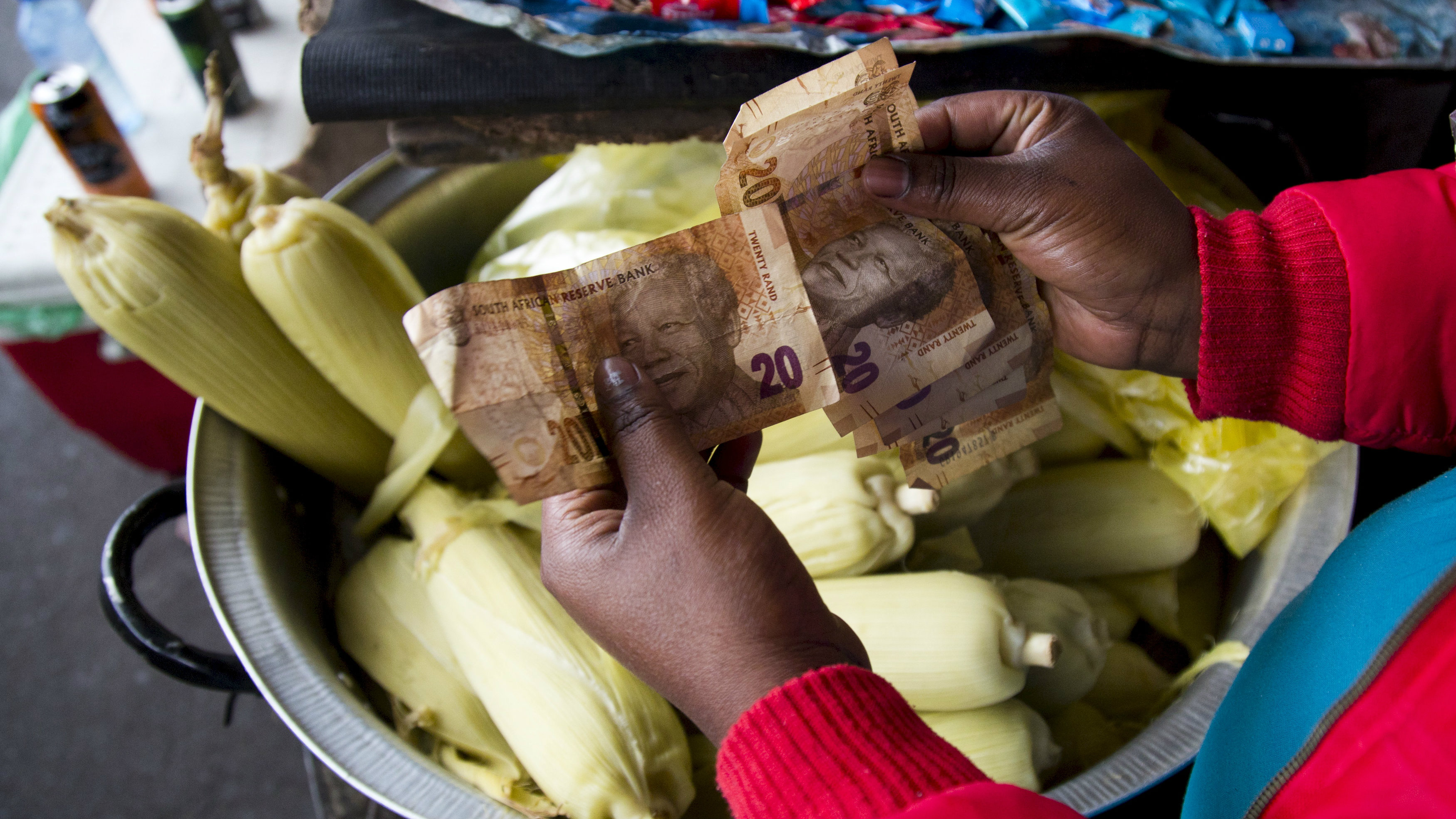 A street trader counts out change for a customer in Durban, September 8, 2015. South Africa's rand firmed more than 1 percent against the dollar, recovering from record lows in the previous session as bets on a rate hike in United States faded due to worries over global growth. The rand rose 1.04 percent to 13.8150 per dollar.