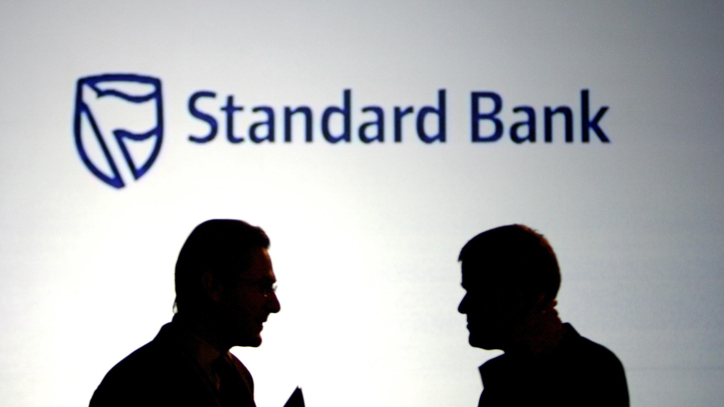 Businessmen chat in front of a Standard Bank logo in Sandton outside Johannesburg October 25, 2007.