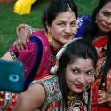 Indian Hindu married women take a selfie from a mobile phone after performing rituals on Karva Chauth festival in Ahmadabad, India, Friday, Oct. 30, 2015. Married women decorate their hands with henna on Karva Chauth festival and observe a fast to pray for the longevity and well being of their husbands. (AP Photo/Ajit Solanki)