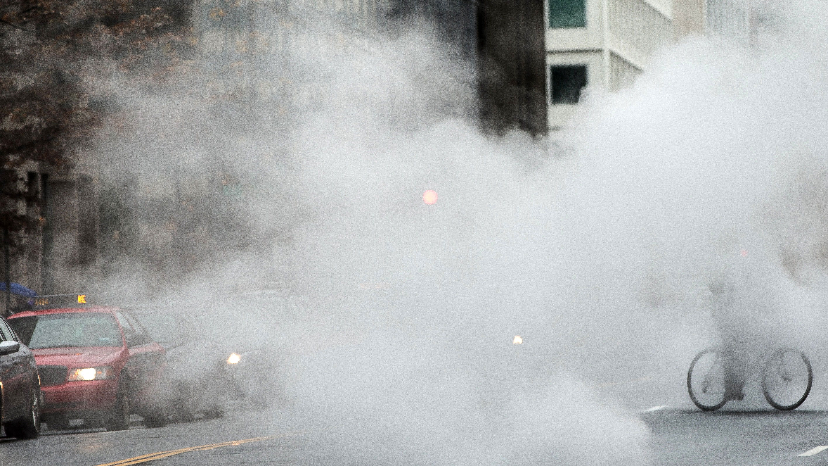 A bicyclist rides through steam vents along 17th Street in Northwest Washington, Monday, Nov. 30, 2015. (AP Photo/Andrew Harnik)